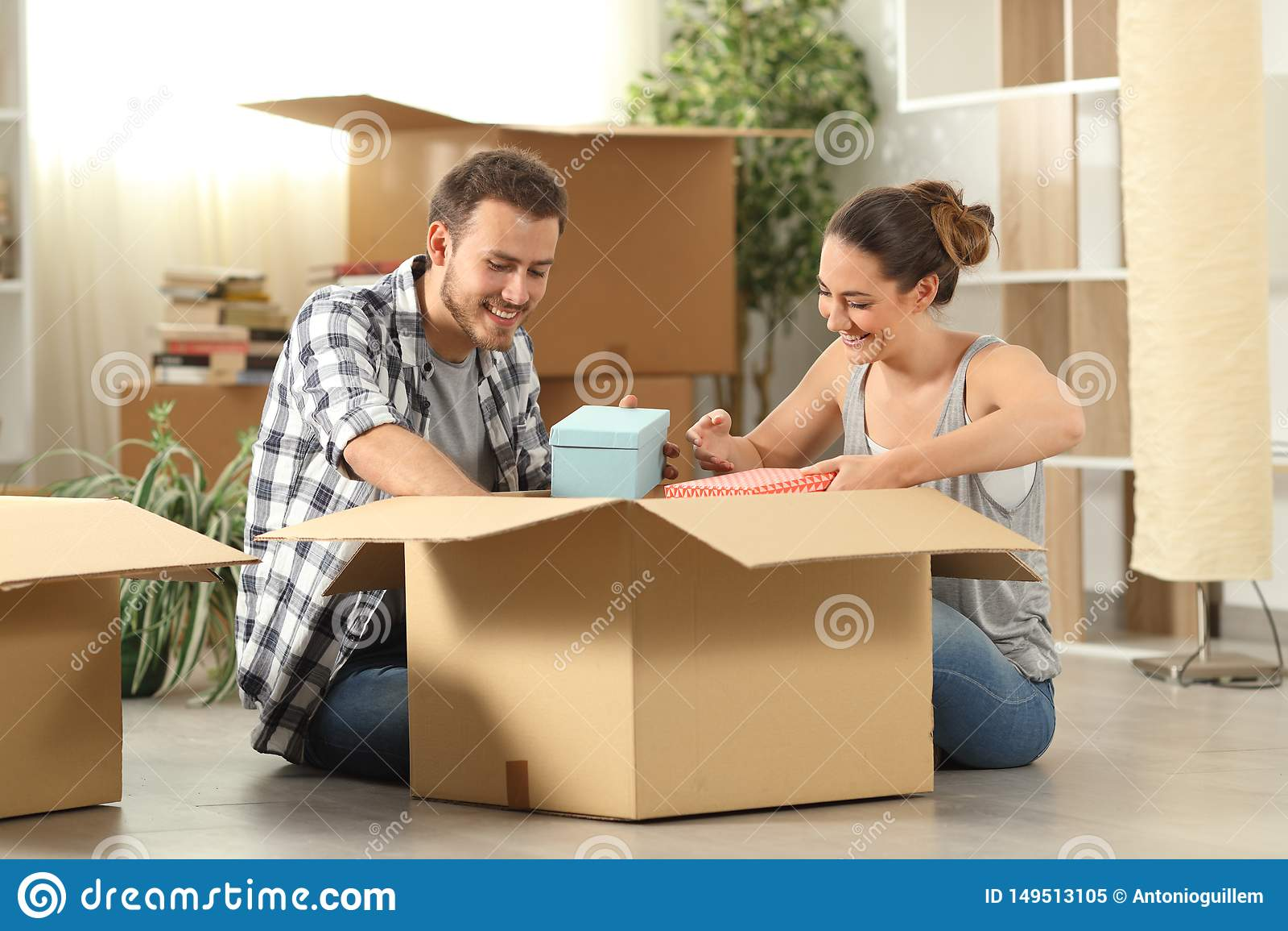 Gelukkige paar unboxing bezittingen die zich naar huis bewegen