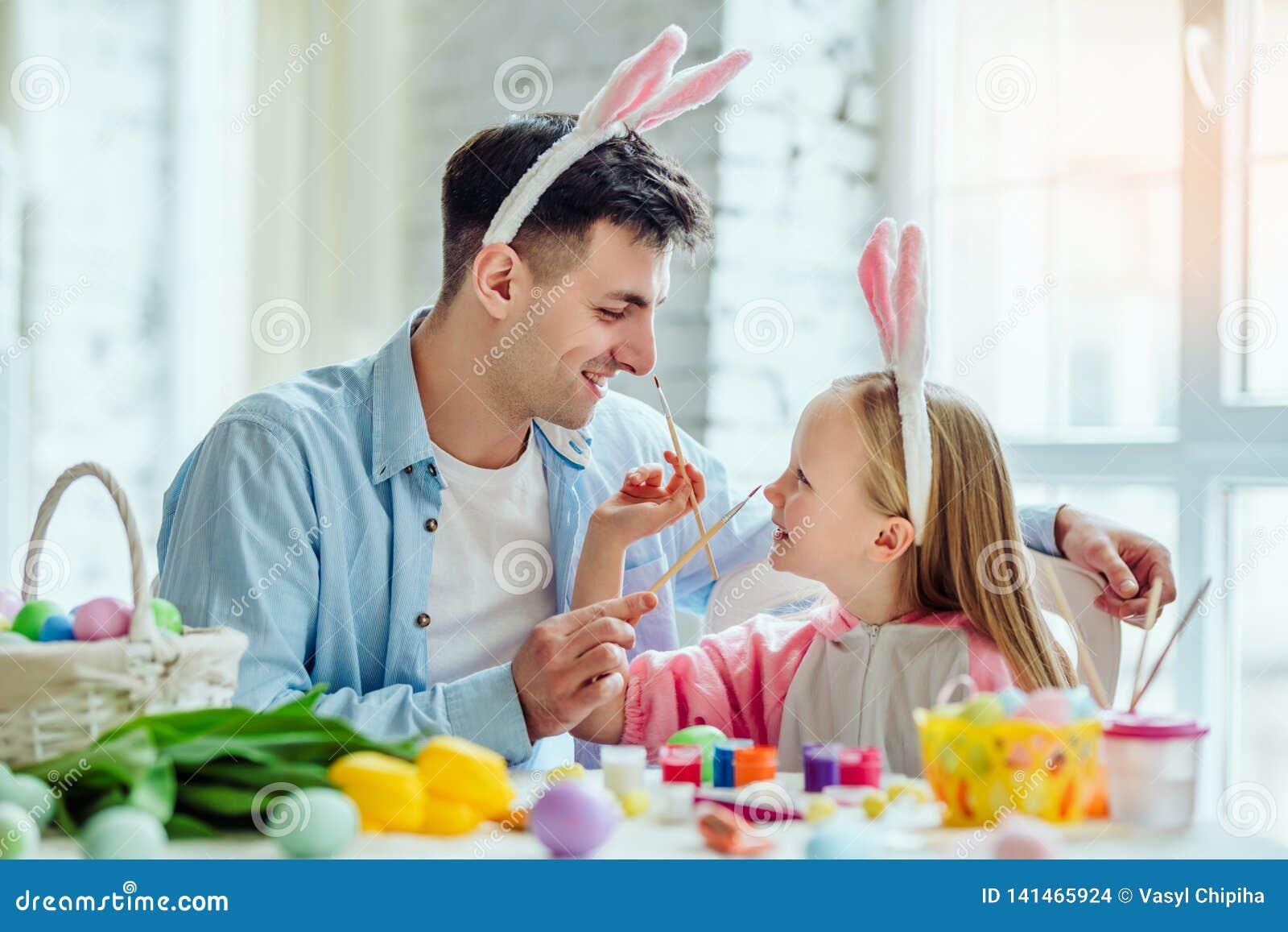 Gelukkige Pasen! De papa en zijn kleine dochter hebben samen pret terwijl het voorbereidingen treffen voor Pasen-vakantie Op de l