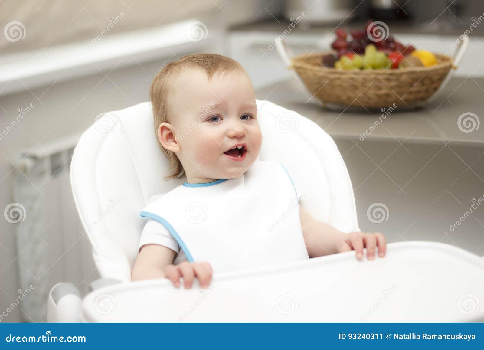 Gelukkige peuterzitting in highchair en het eten van havermoutpap Babyweiland