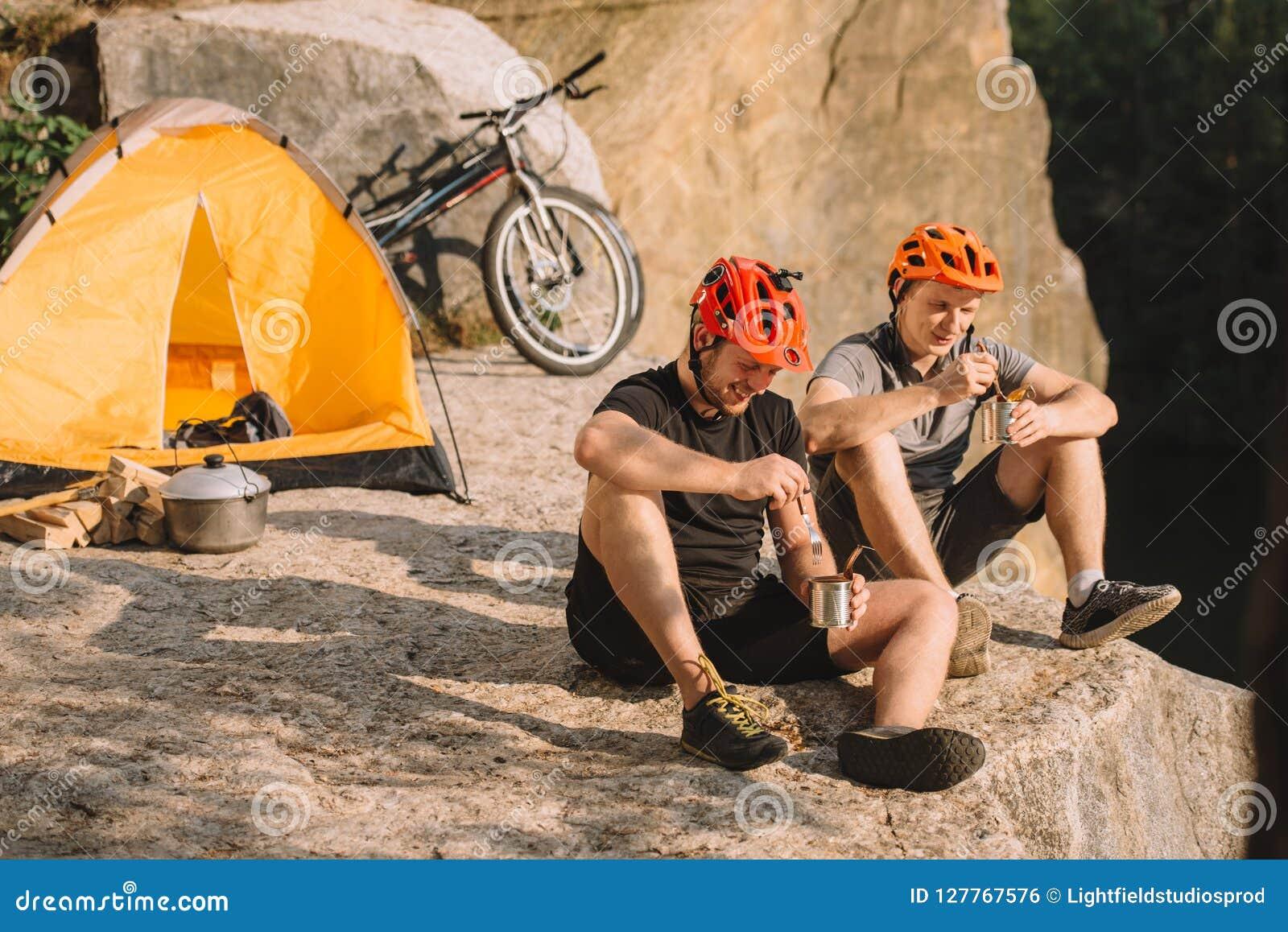 Gelukkige proeffietsers die ingeblikt voedsel in het kamperen eten