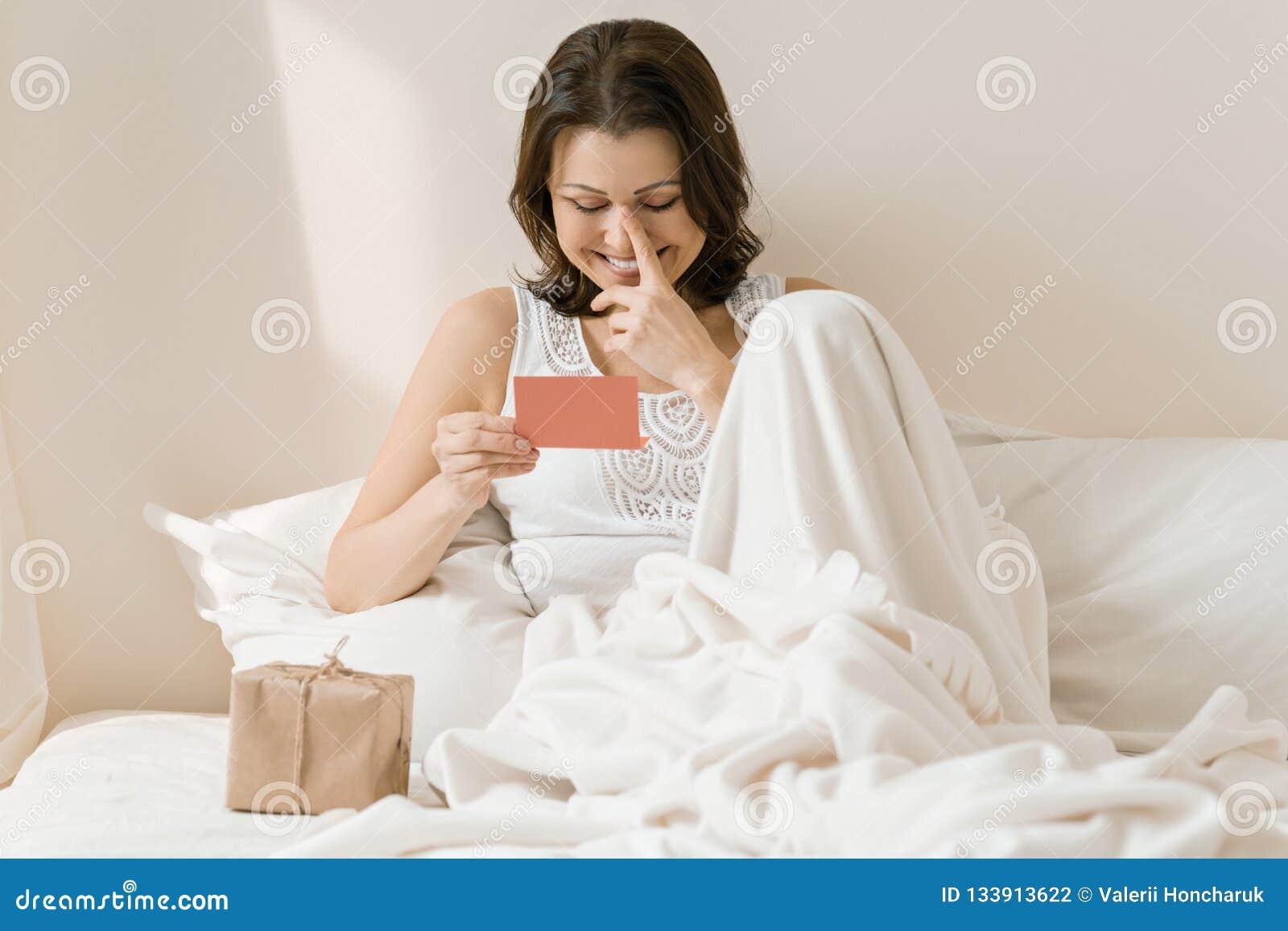 Gelukkige rijpe vrouw thuis in bed met de kaart van de de lezingsgroet van de verrassingsgift Emotie van geluk, vreugde, verrassi