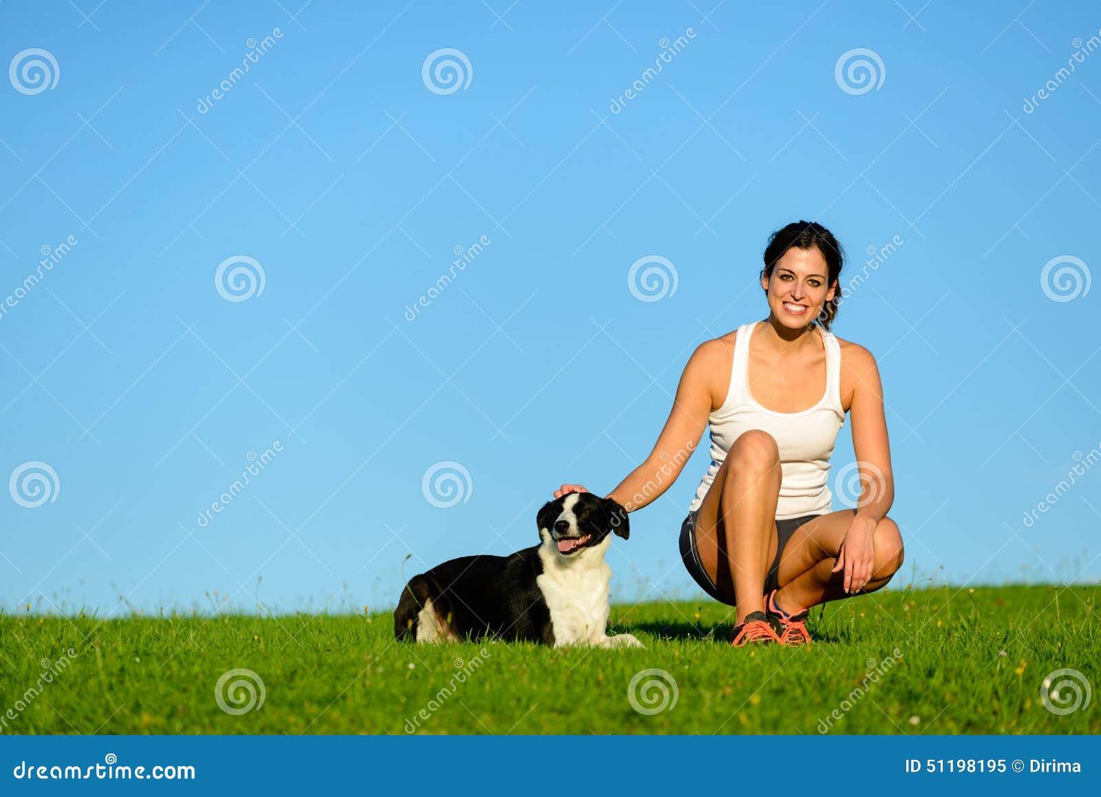 Gelukkige sportieve vrouw die een het uitoefenen rust met haar hond nemen