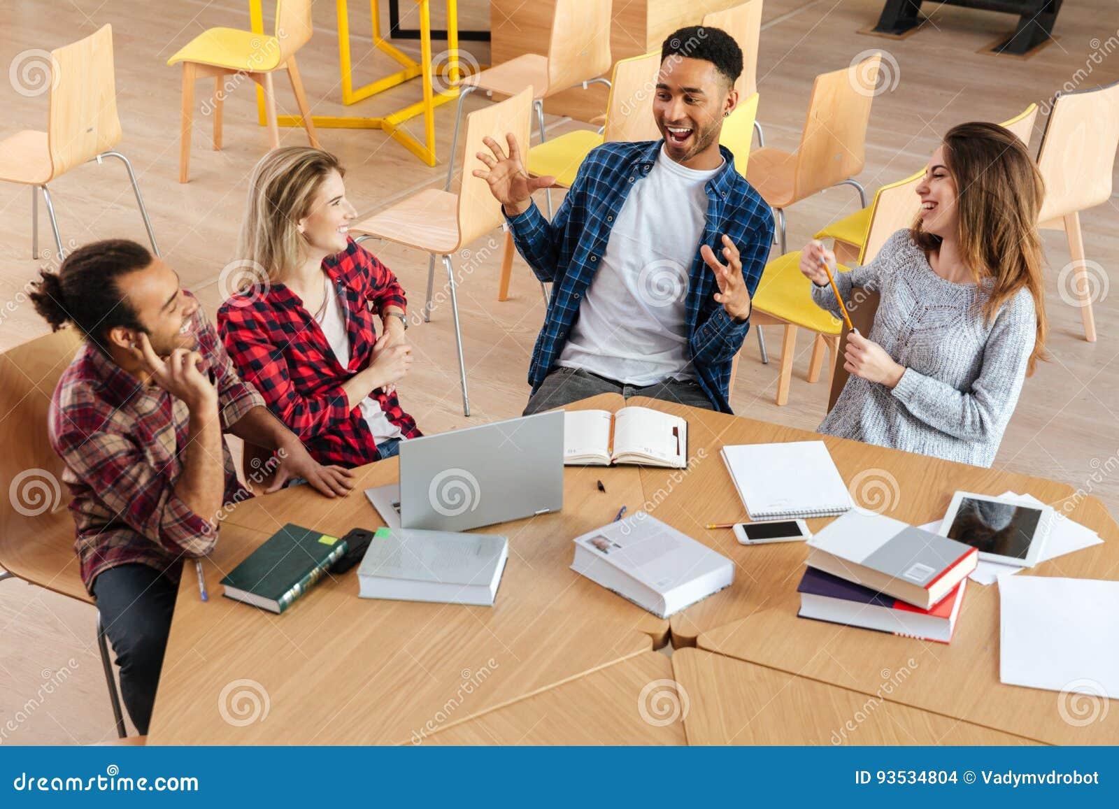 Gelukkige studenten die in bibliotheek het spreken met elkaar zitten