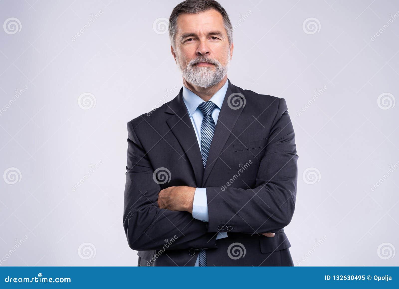Gelukkige tevreden rijpe zakenman die die camera bekijken op witte achtergrond wordt geïsoleerd