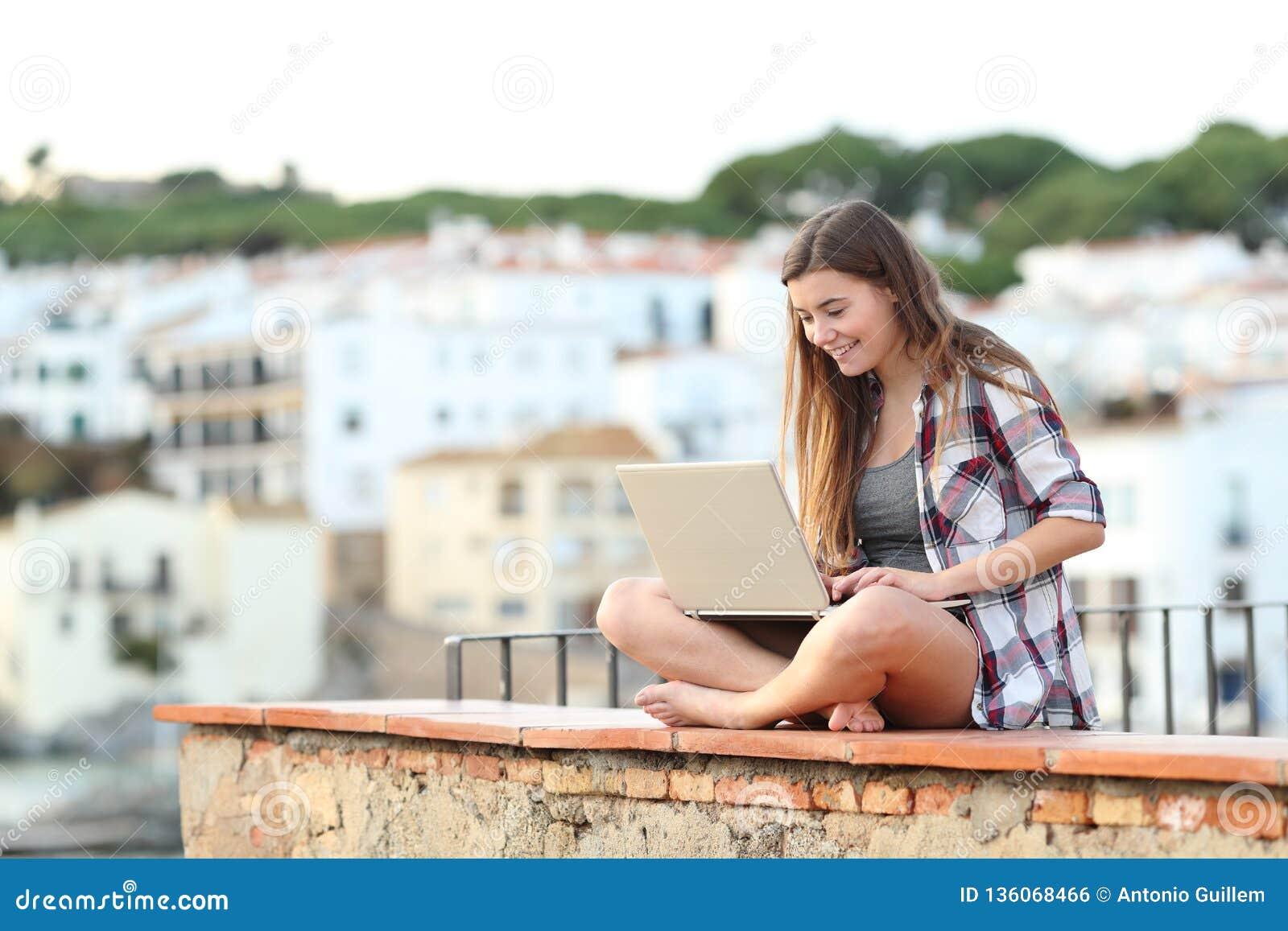 Gelukkige tiener die een laptop zitting op een richel op een stad gebruiken