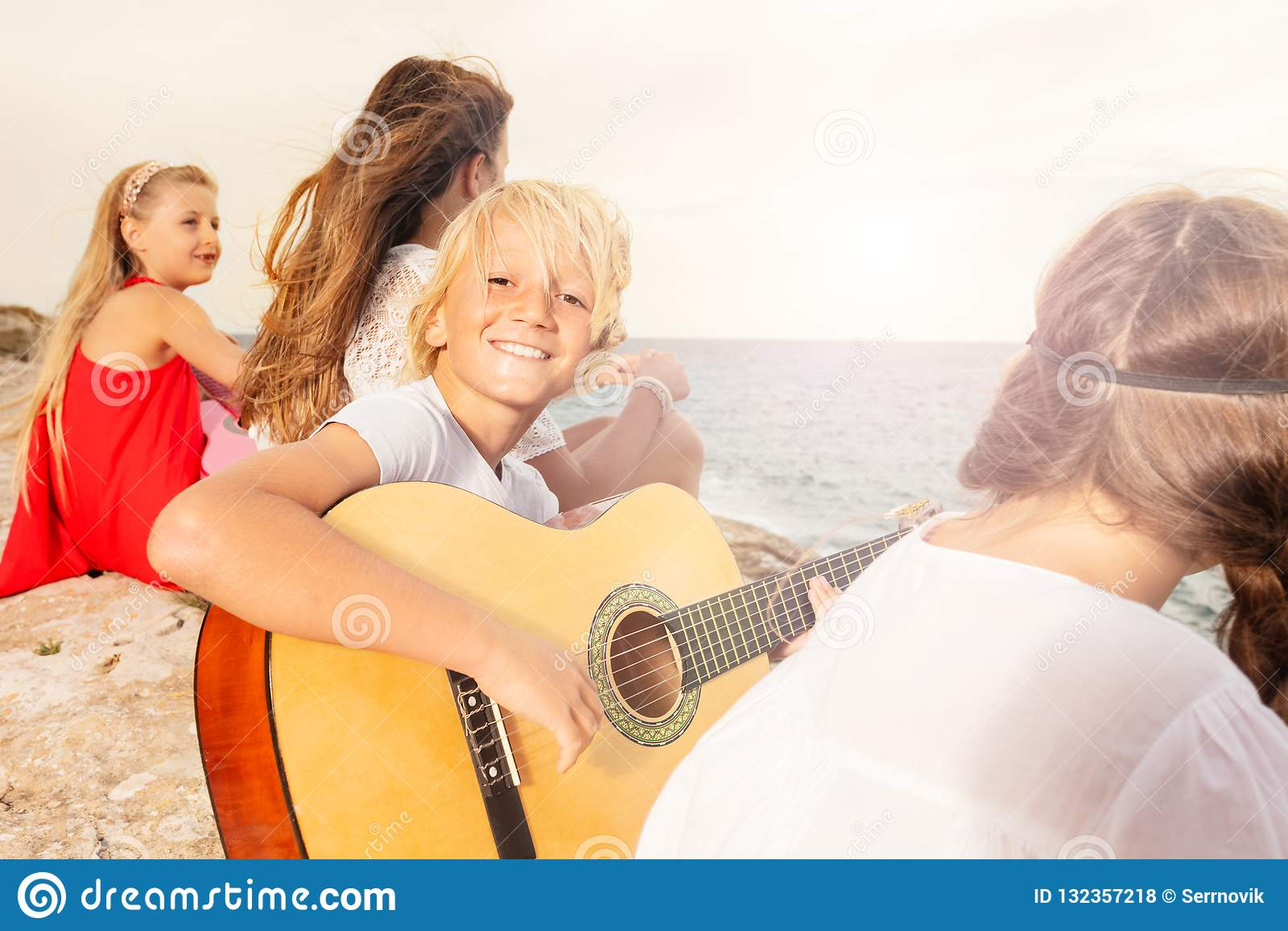 Gelukkige tiener het spelen gitaar op het strand