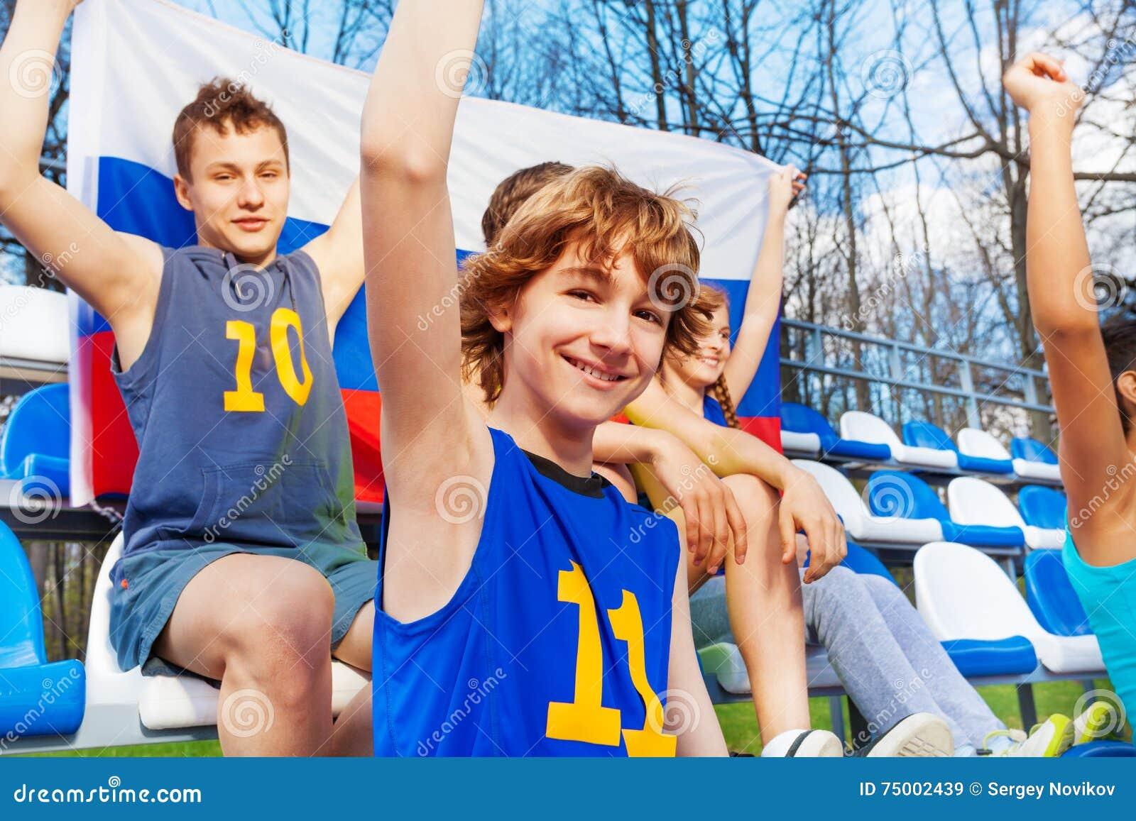 Gelukkige tienersportventilators met Russische vlag
