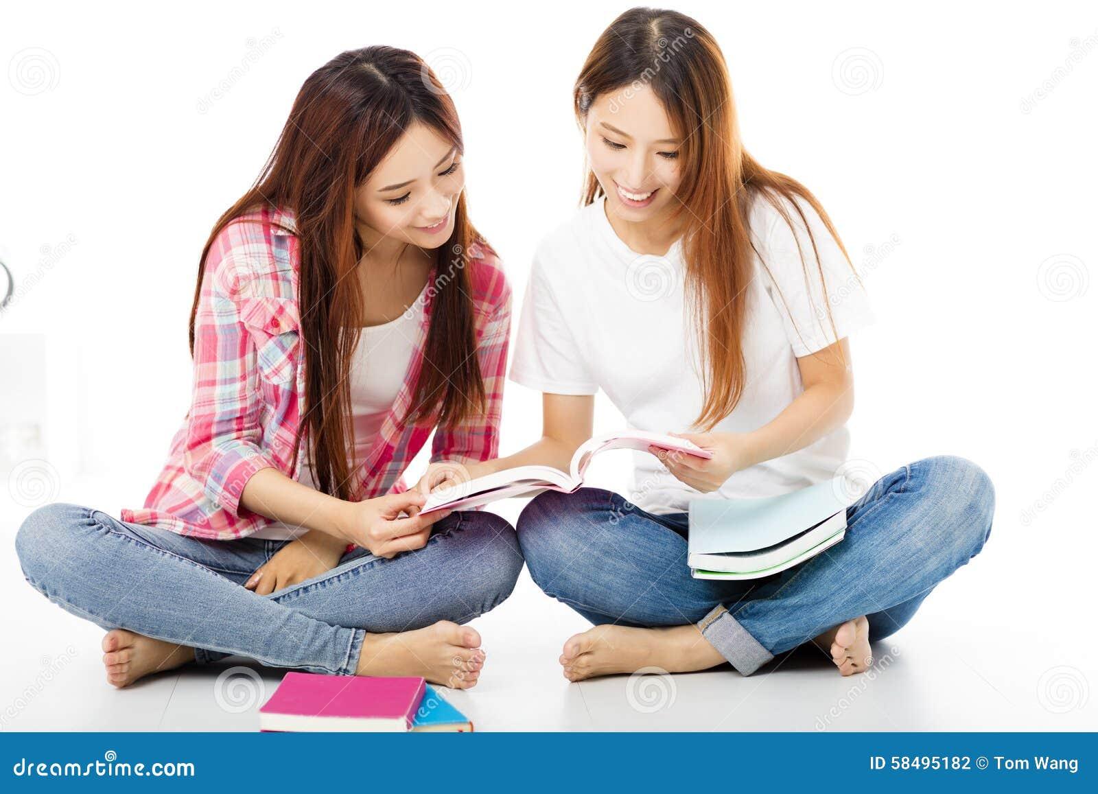 Gelukkige tienerstudentenmeisjes die op de boeken letten