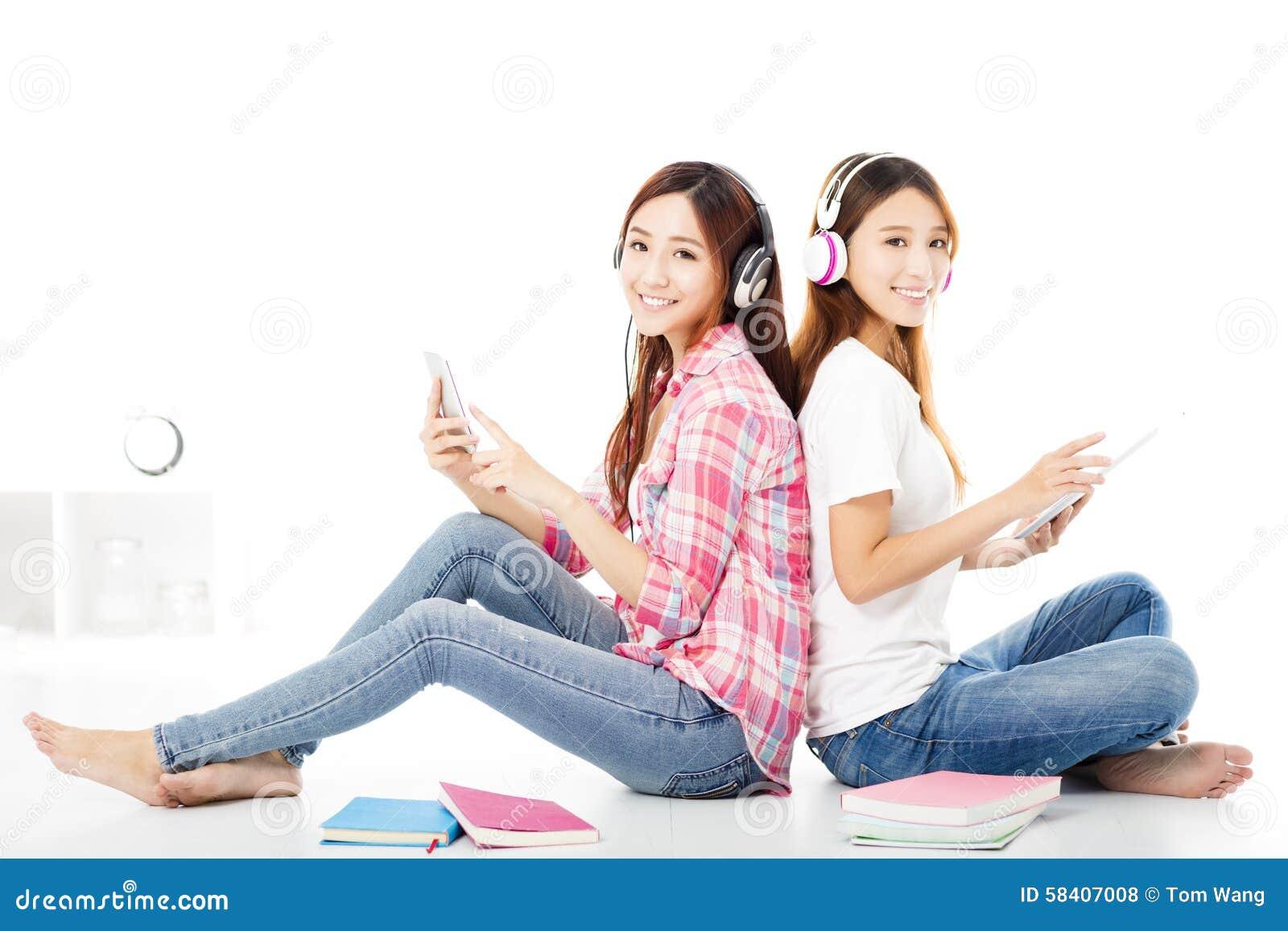 Gelukkige tienerstudentenmeisjes die op de vloer zitten