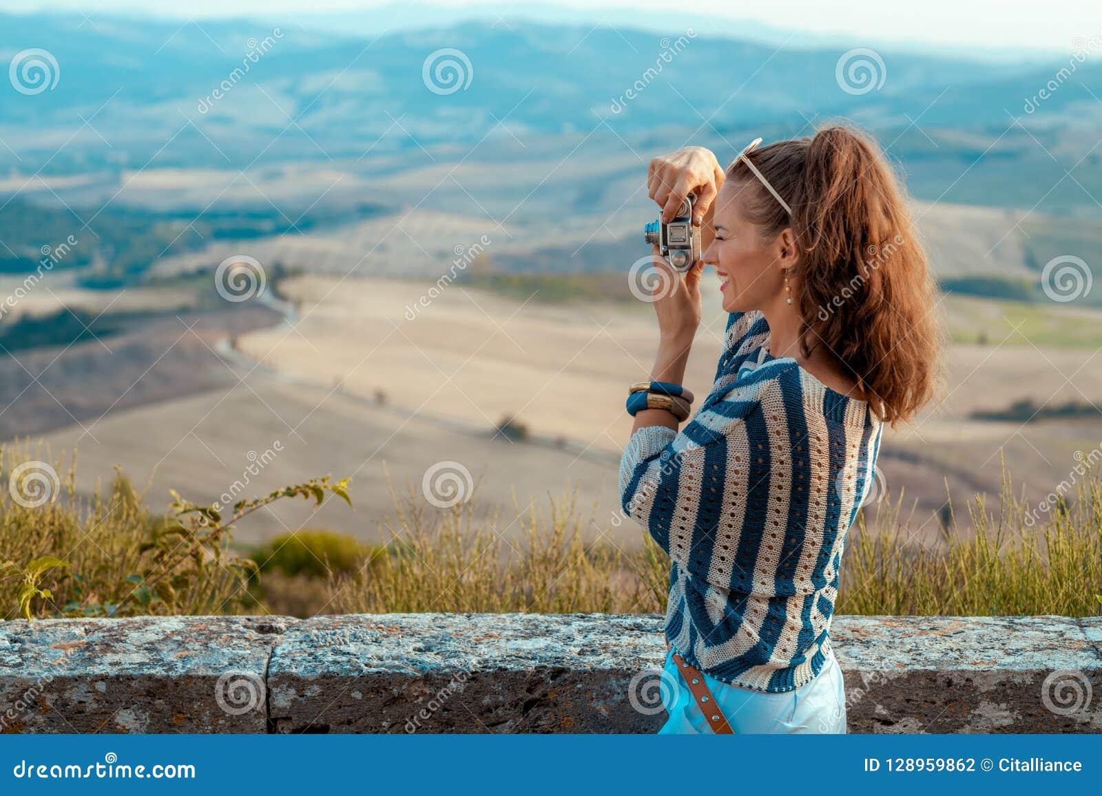 Gelukkige toeristenvrouw die foto s met retro fotocamera nemen