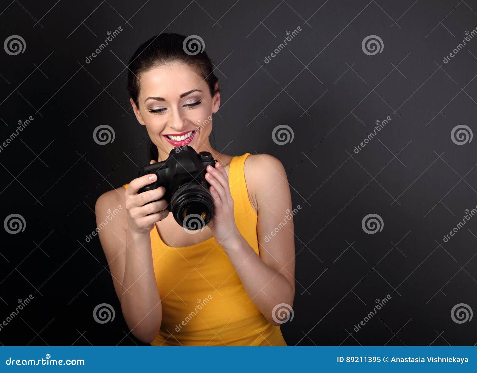 Gelukkige toothy het glimlachen jonge vrouwelijke foto in gele hoogste holdi