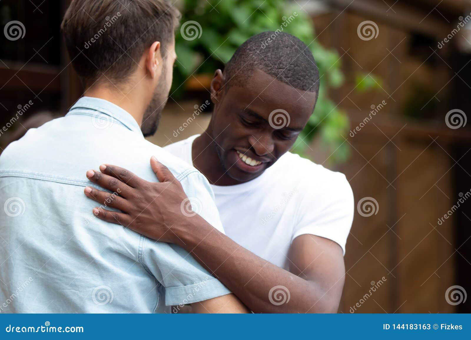Gelukkige twee multiraciale mannelijke beste vrienden die het omhelzen begroeten op vergadering