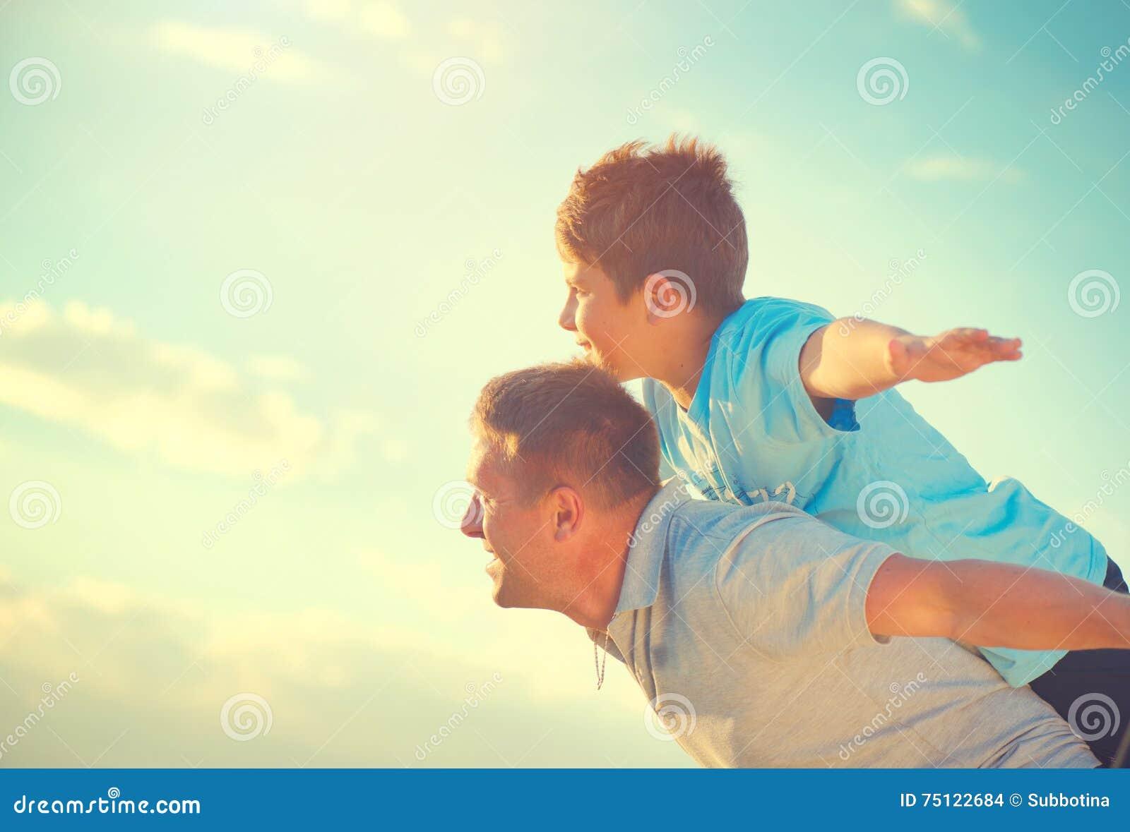 Gelukkige vader en zoon die pret over mooie hemel hebben