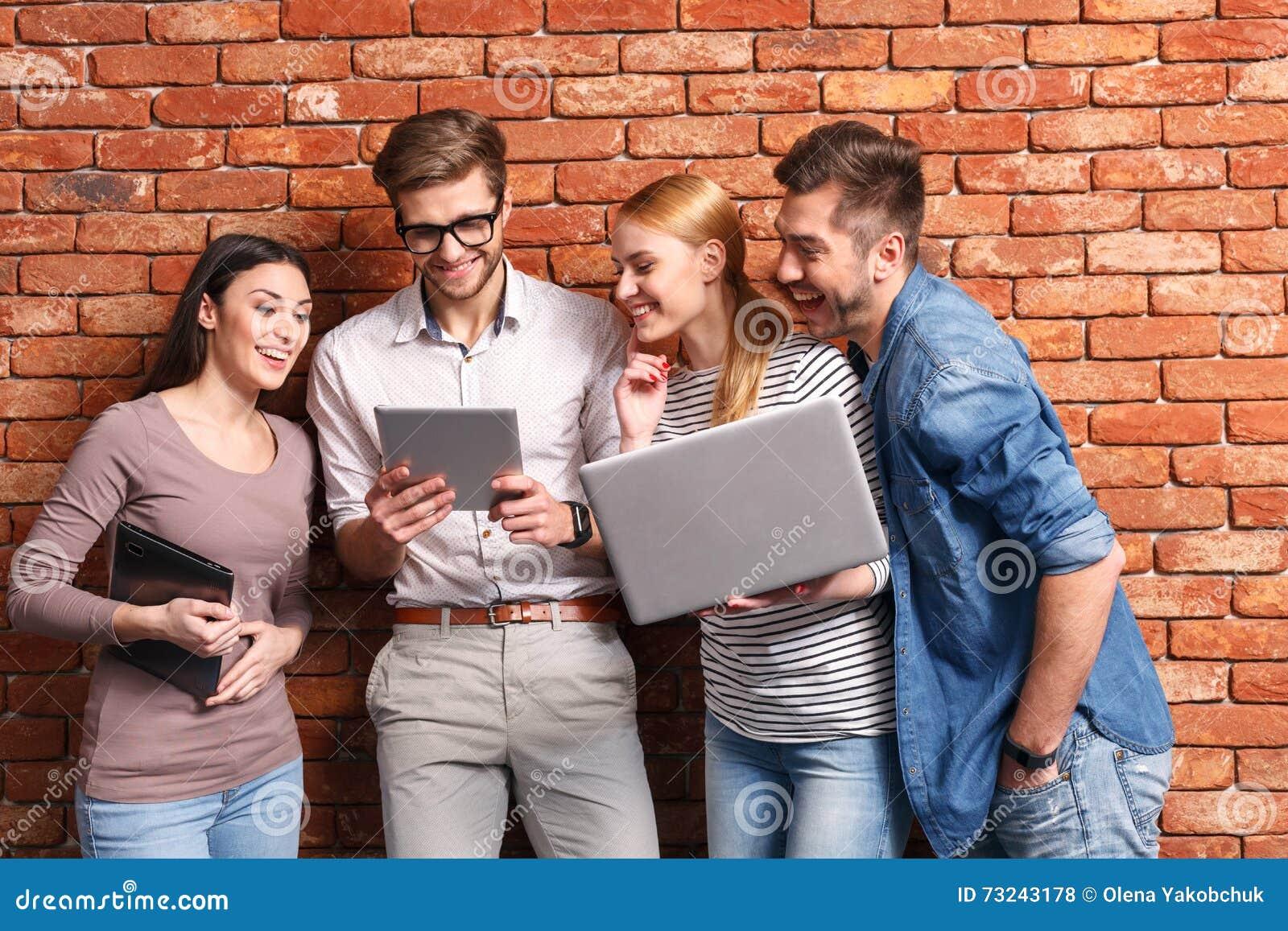Gelukkige vier vrienden die moderne gadgets gebruiken
