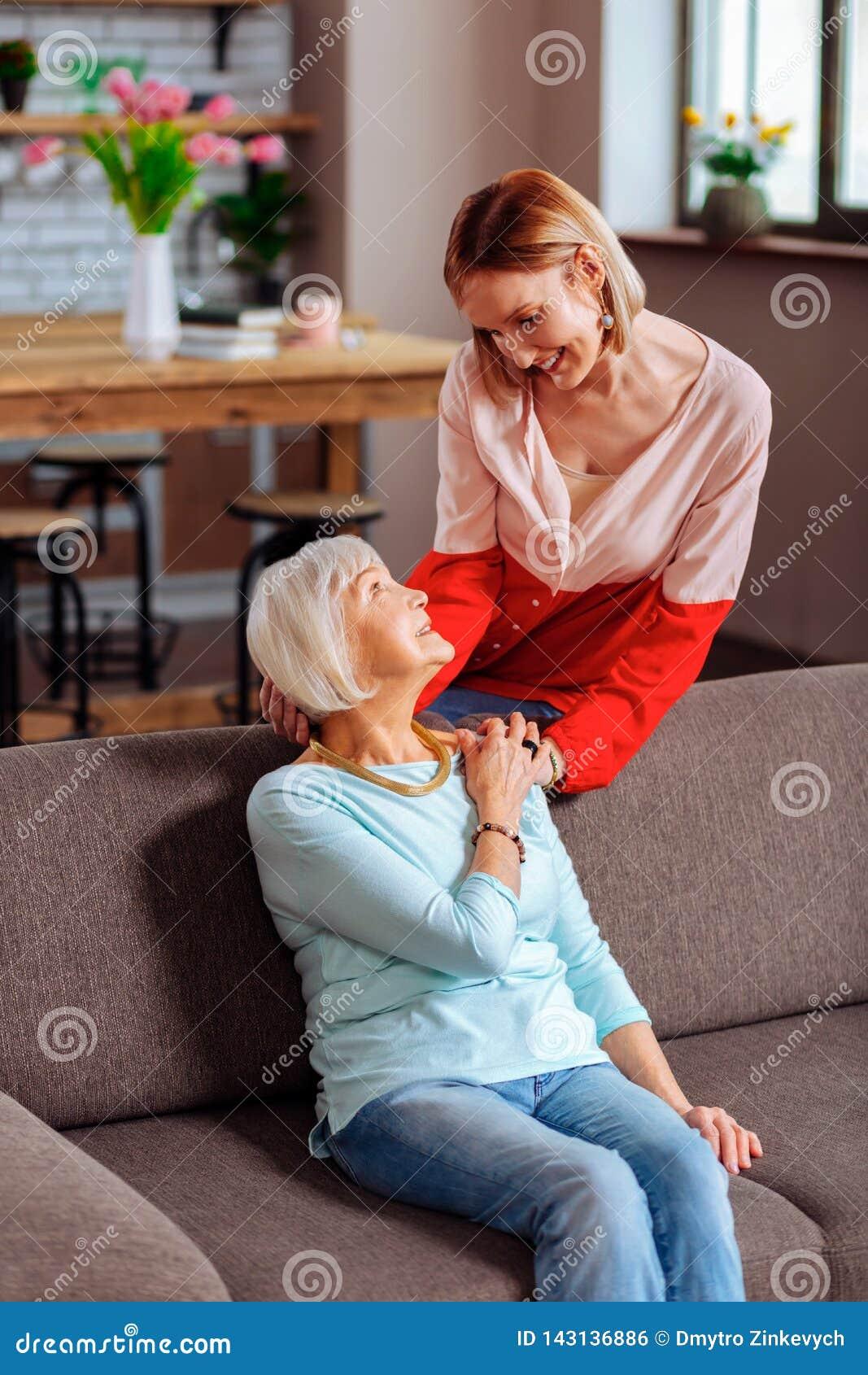Gelukkige volwassen dame die teder moederhand palming en hoofd houdt