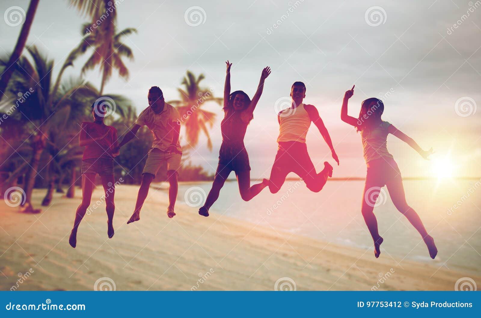 Gelukkige vrienden die en op strand dansen springen
