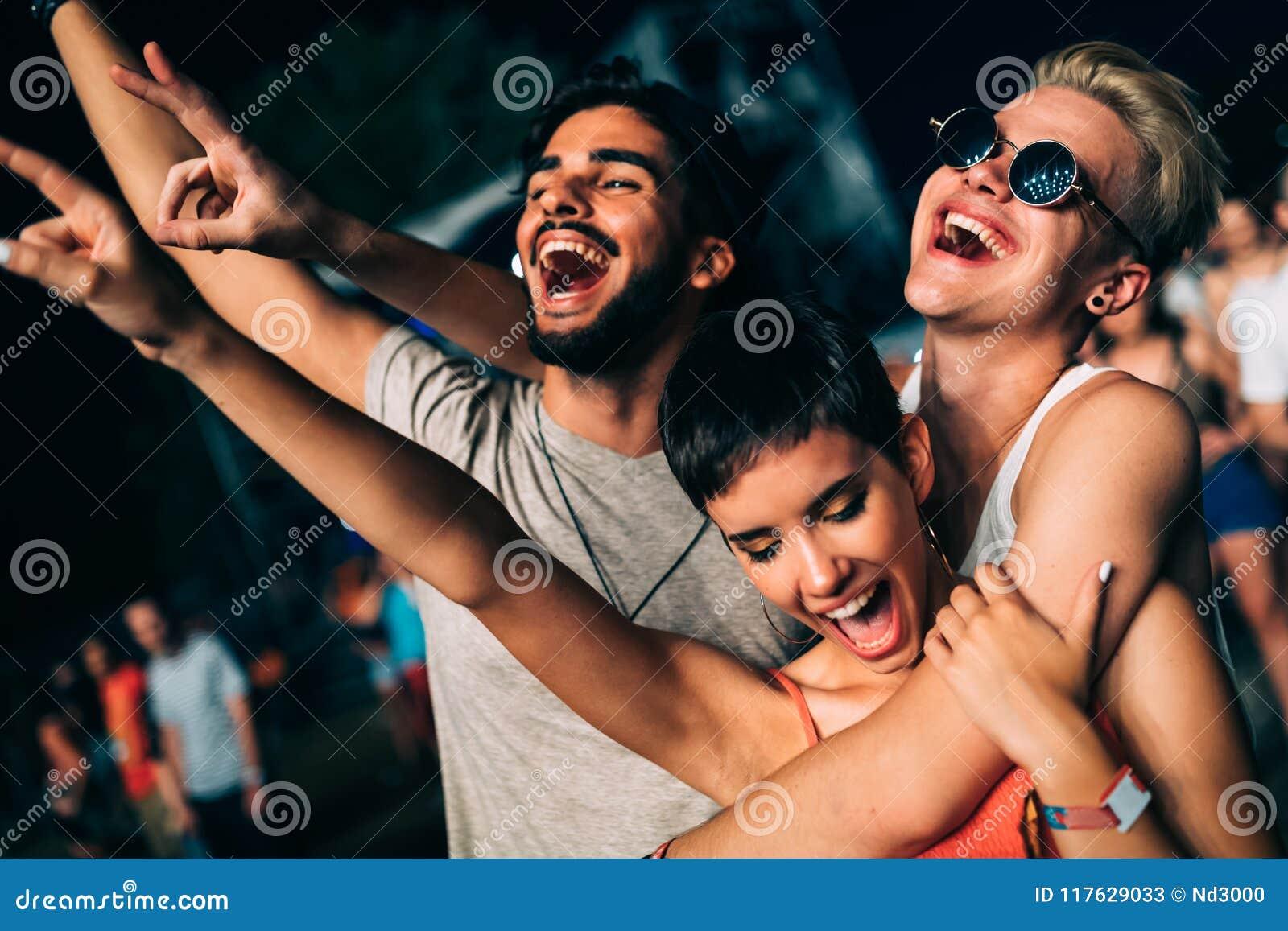 Gelukkige vrienden die pret hebben bij muziekfestival