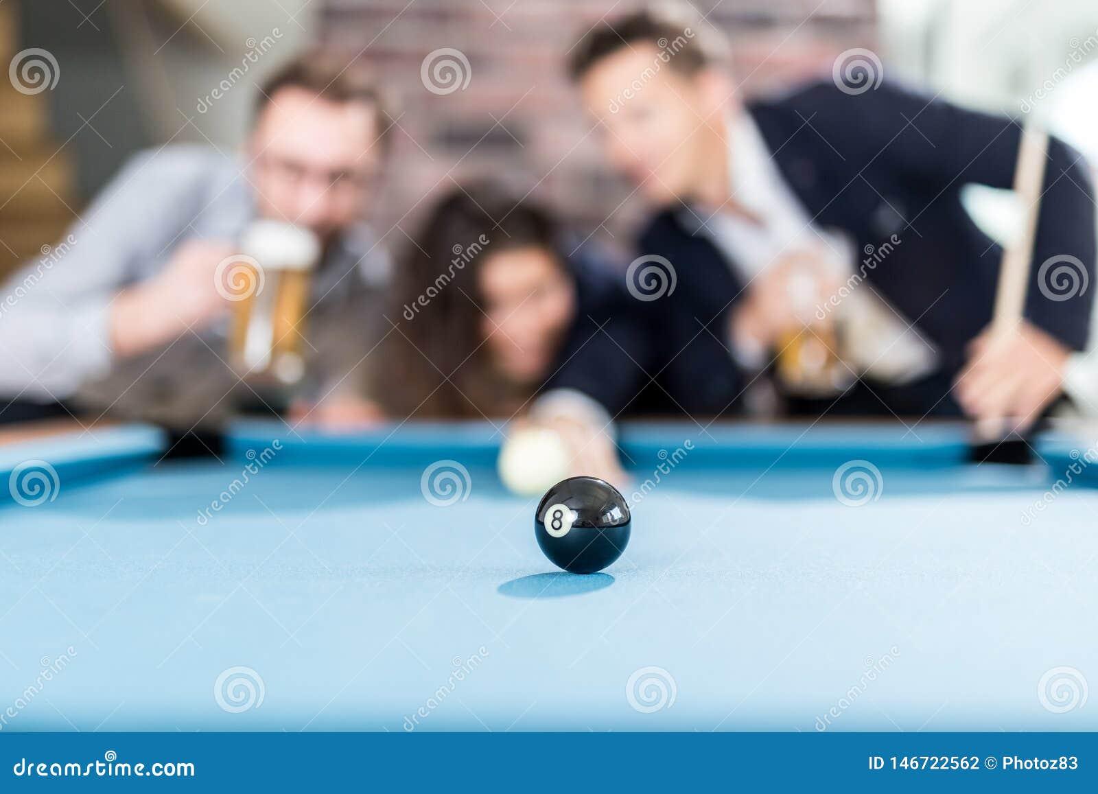 Gelukkige vrienden die spelend snookerspel en drinkend bier genieten van