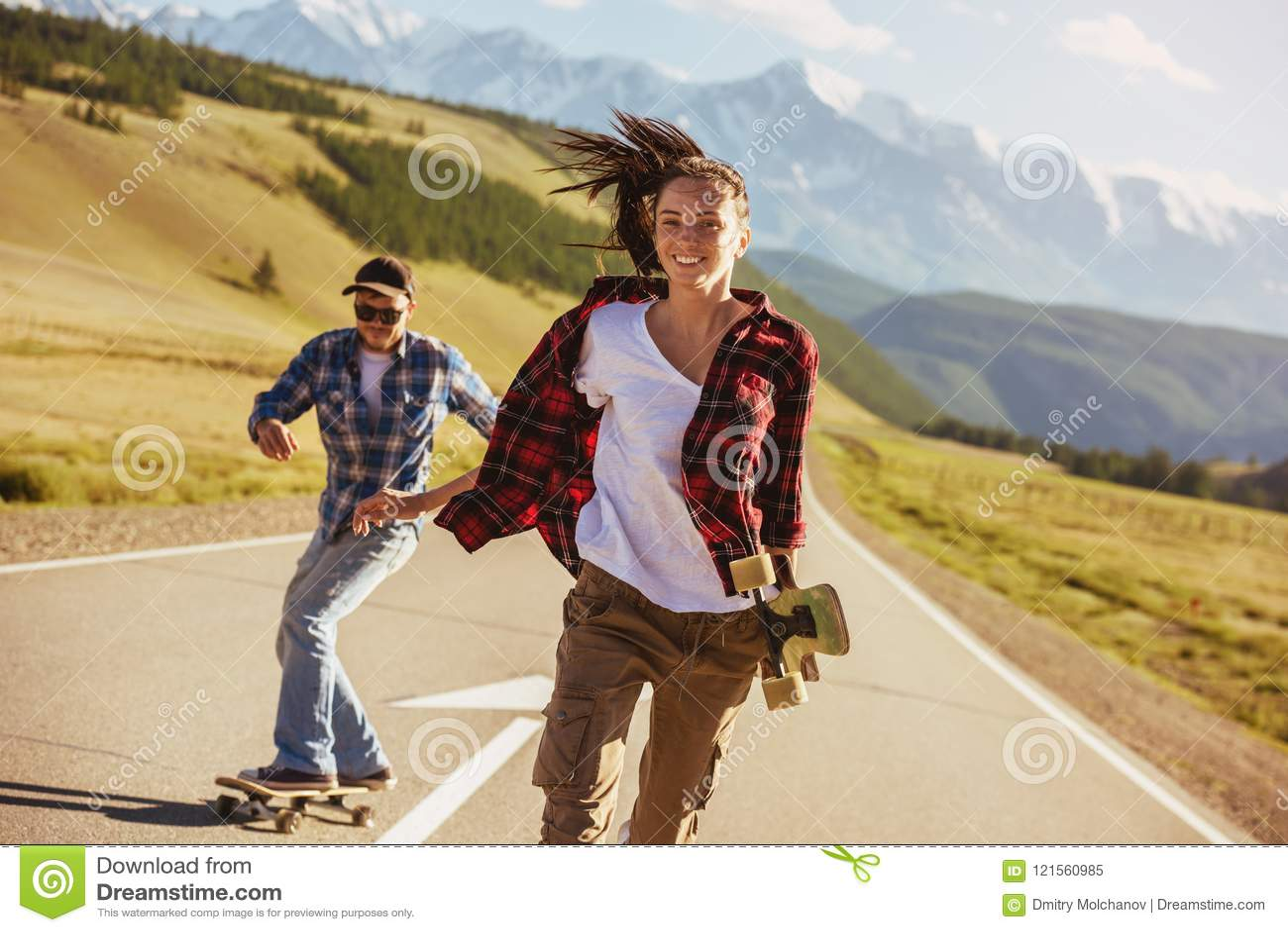Gelukkige vrienden met vleten en longboards bij rechte weg