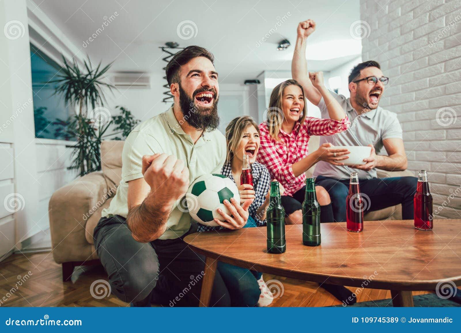 Gelukkige vrienden of voetbalventilators die op voetbal op TV letten