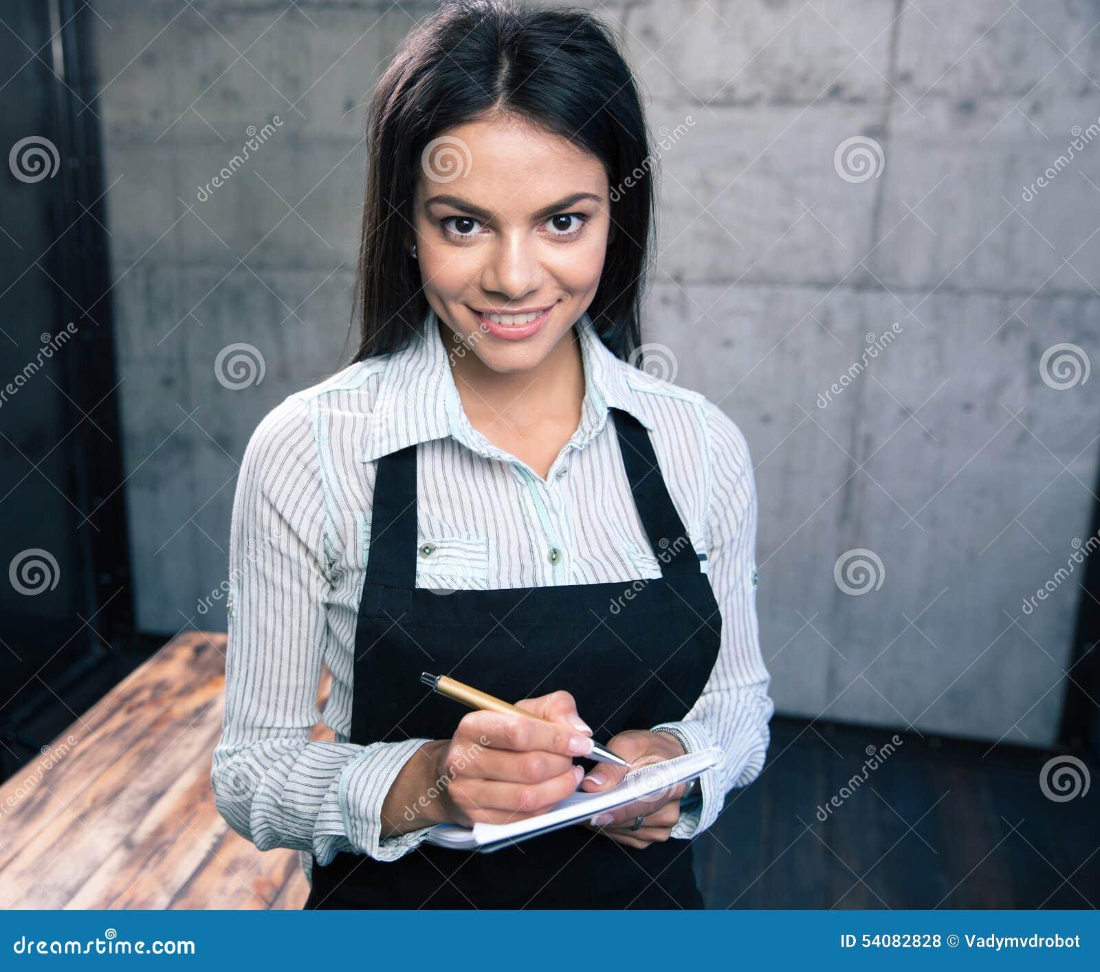 Gelukkige vrij vrouwelijke kelner in schort