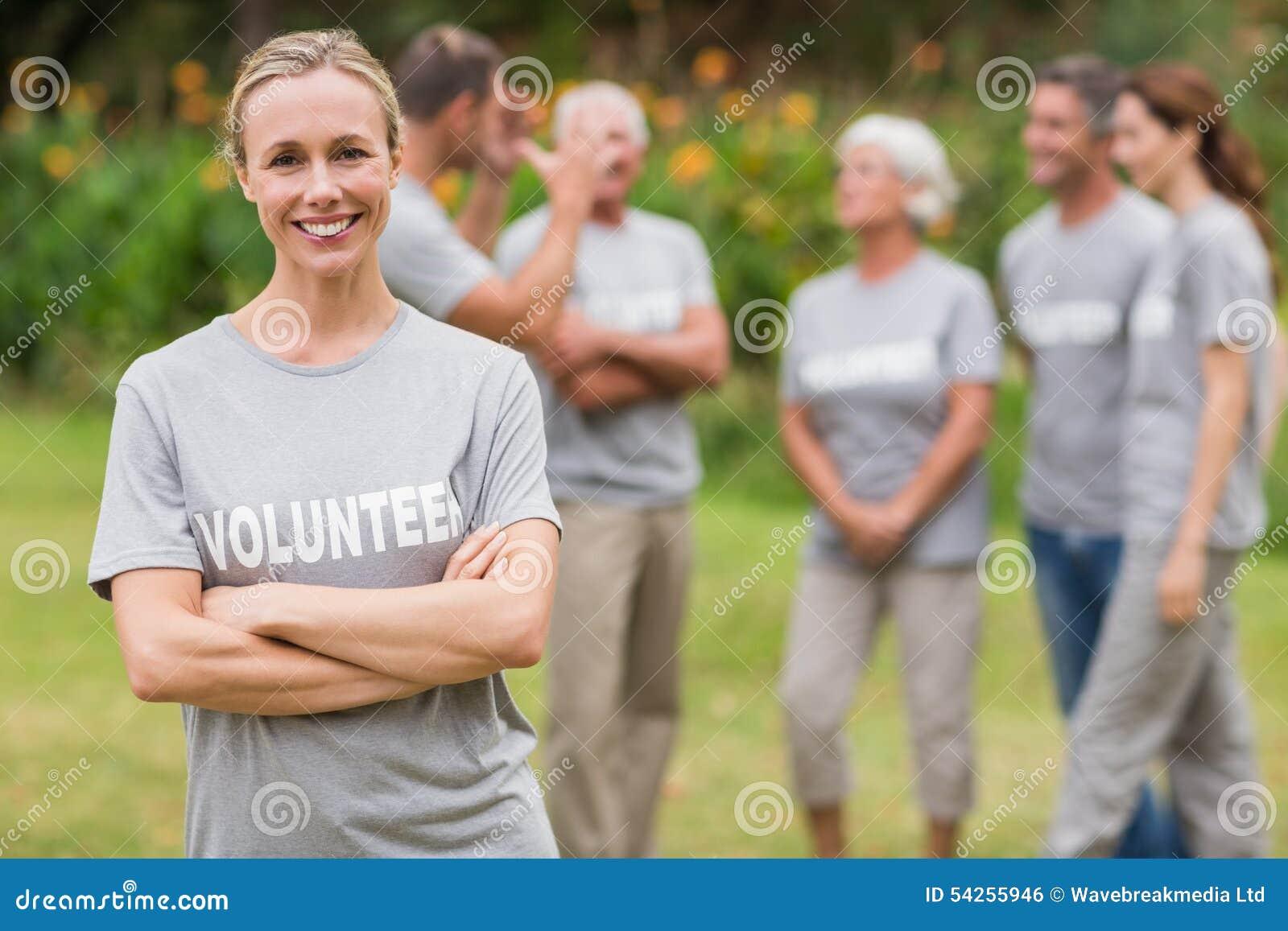Gelukkige vrijwilliger die camera met gekruiste wapens bekijken