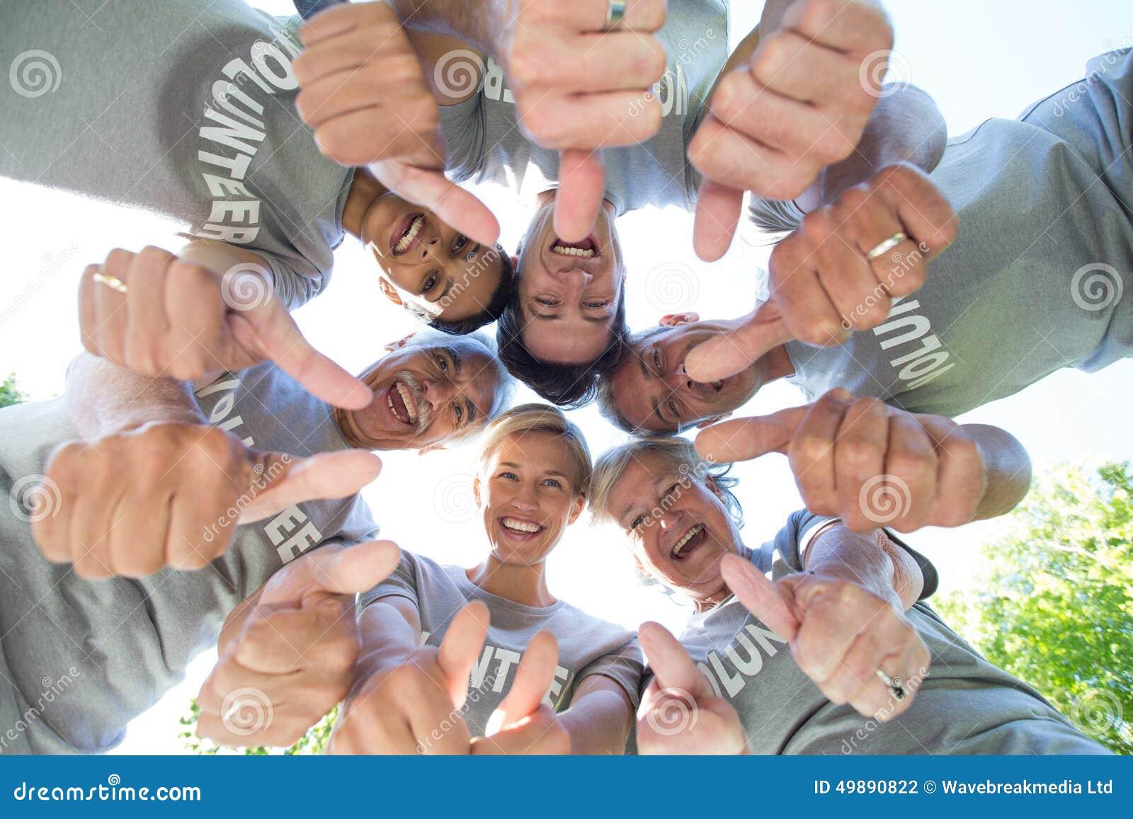 Gelukkige vrijwilligersfamilie die neer met omhoog duimen kijken