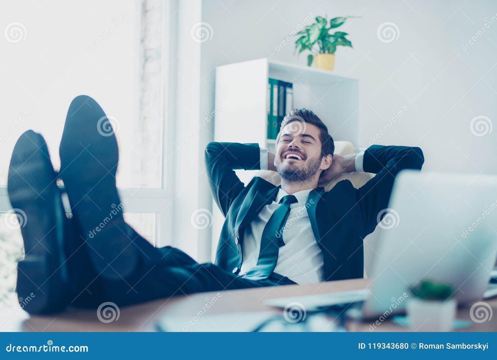 Gelukkige vrolijke glimlachende jonge ondernemer die op stoelwi liggen