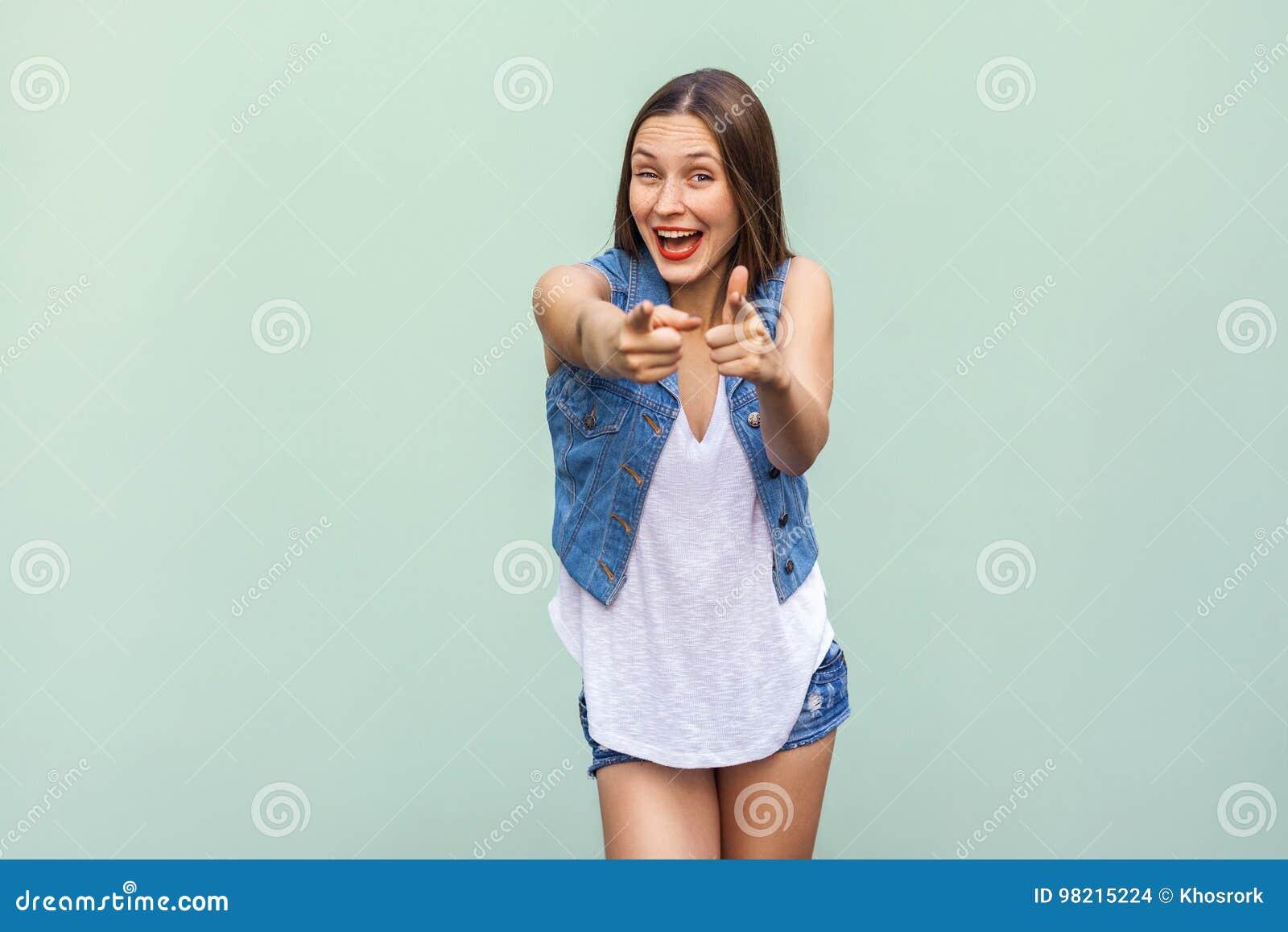Gelukkige vrolijke tiener met sproeten, toevallige stijlkleren die, die en vingers richten op camera binnen bekijken