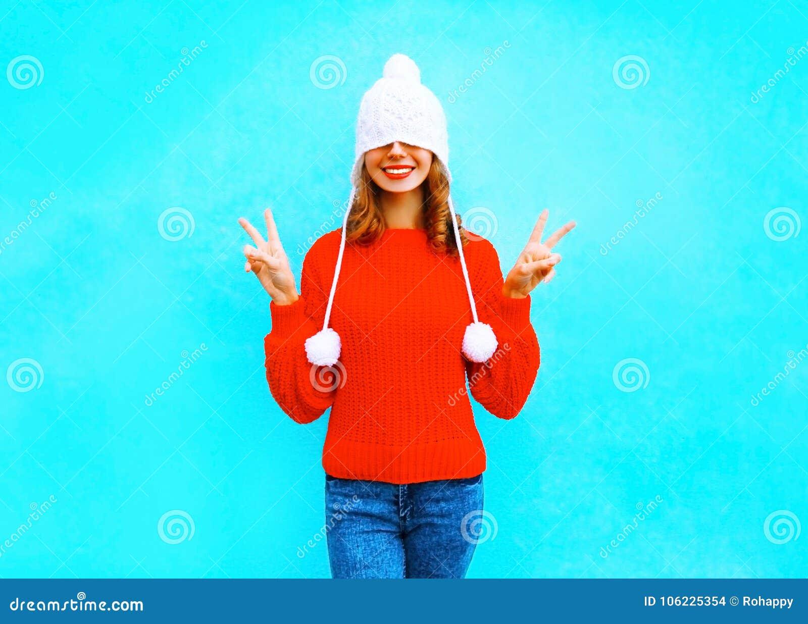 Gelukkige vrolijke vrouw in een gebreide hoed, rode sweater