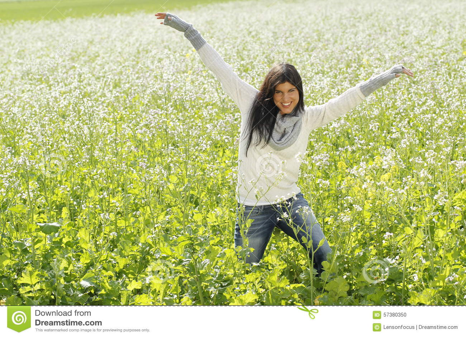 Gelukkige vrouw in aard met uitgestrekte wapens op een bloemgebied