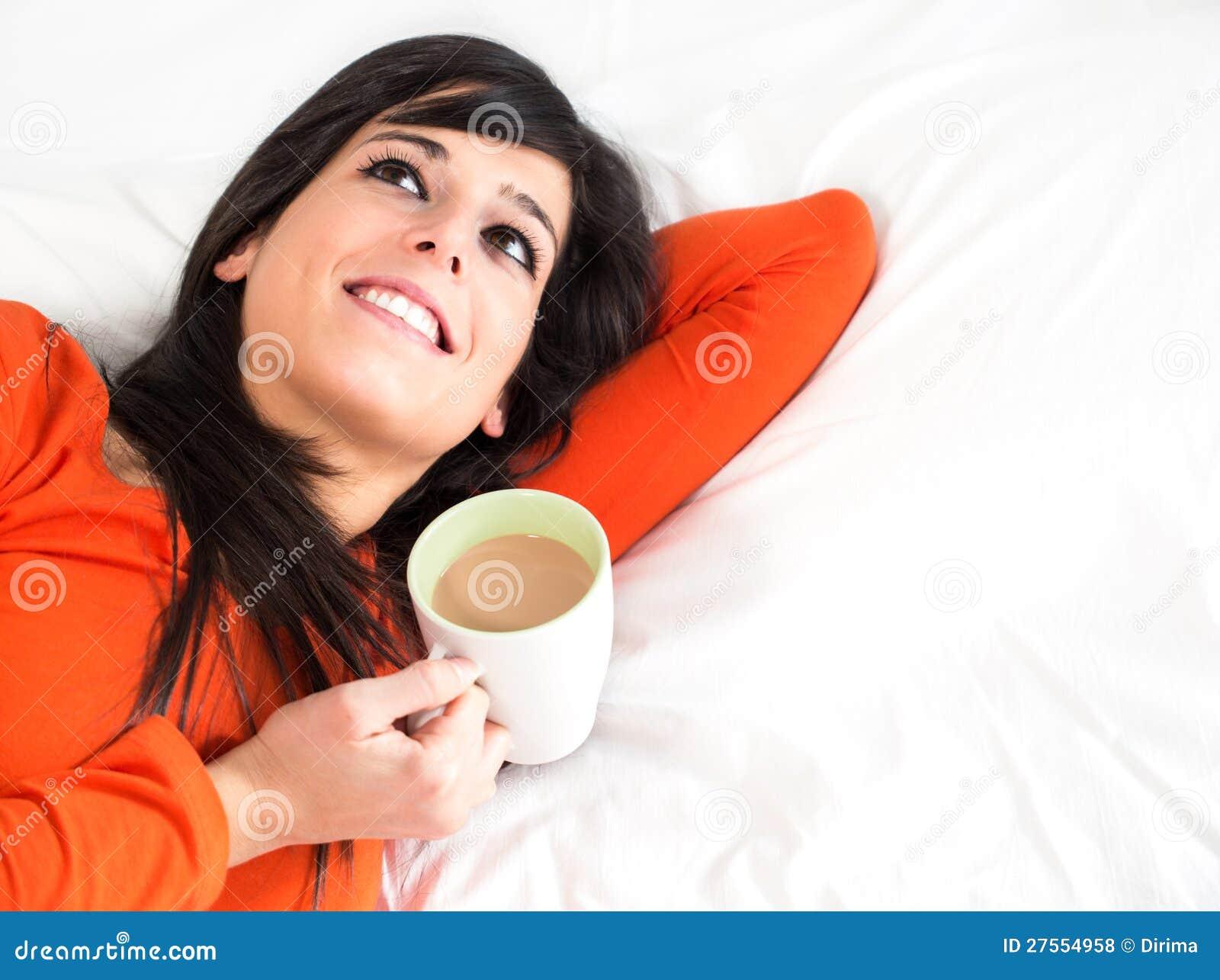 Gelukkige vrouw in bed met kop van koffie