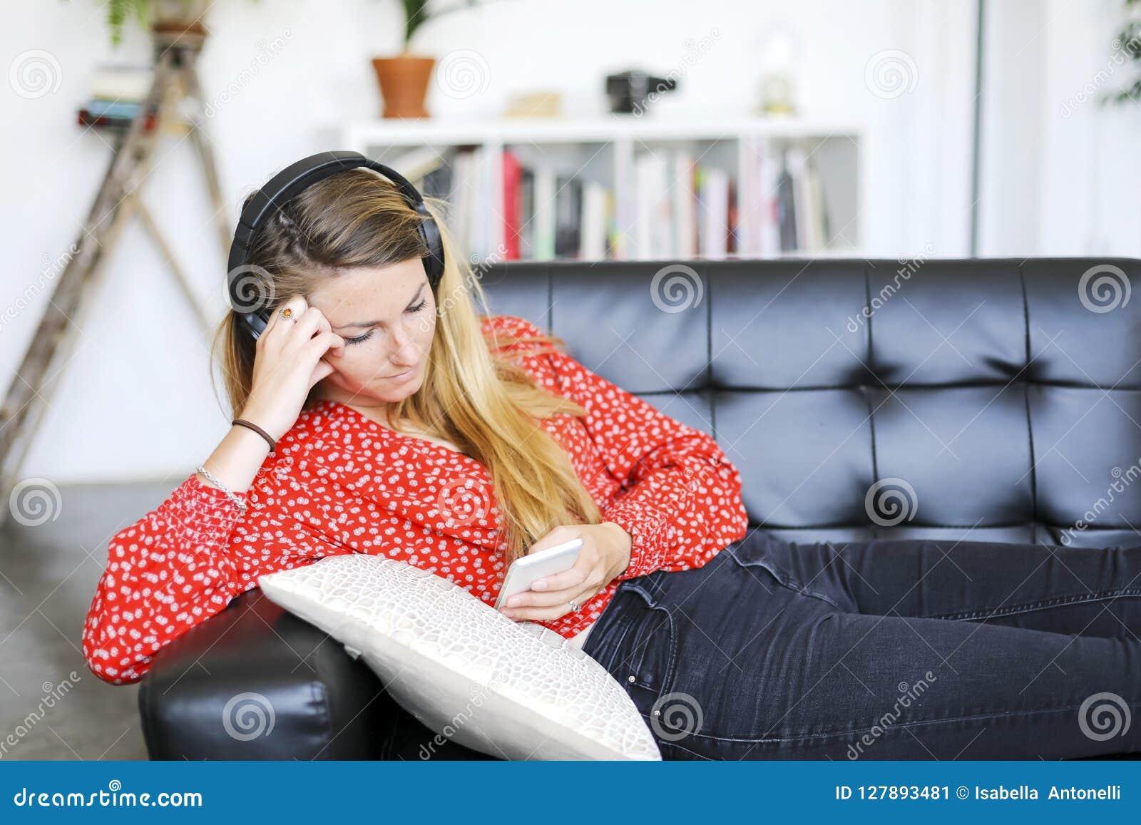 Gelukkige vrouw die aan muziek luisteren die hoofdtelefoons dragen die een smartp gebruiken