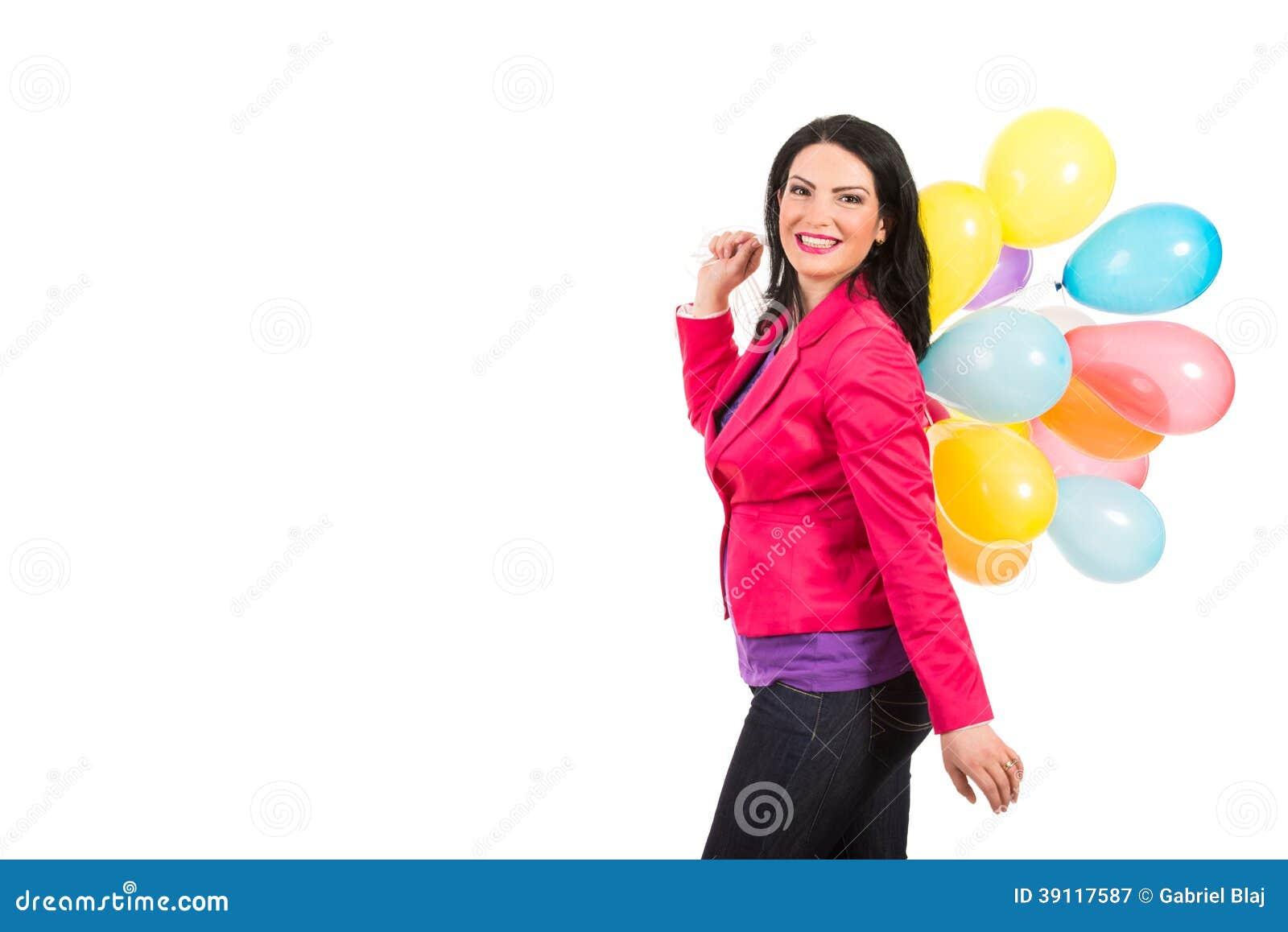 Gelukkige vrouw die en ballons lopen houden