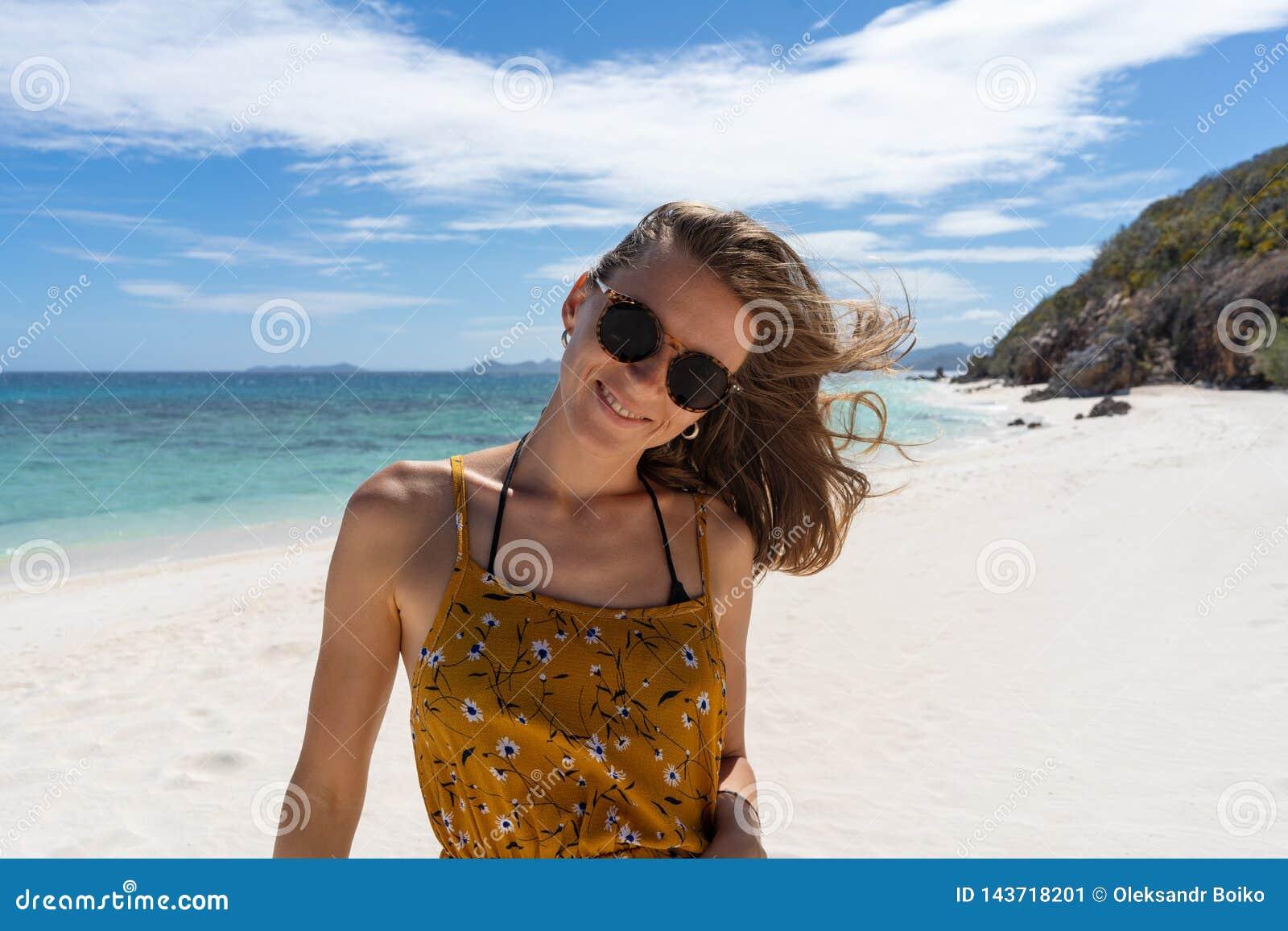 Gelukkige vrouw die en pret glimlachen hebben bij strand
