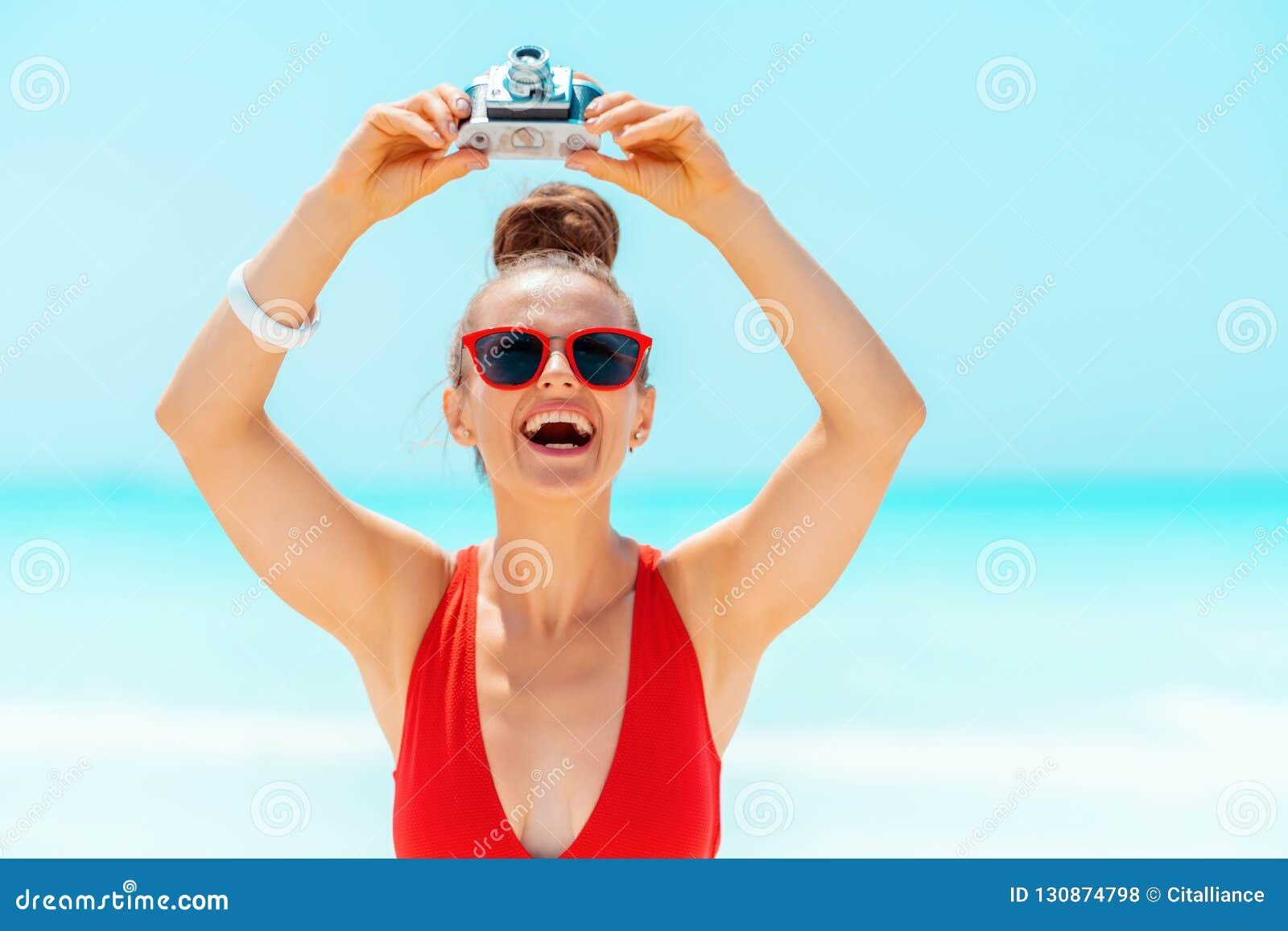Gelukkige vrouw die foto s met retro fotocamera nemen op zeekust