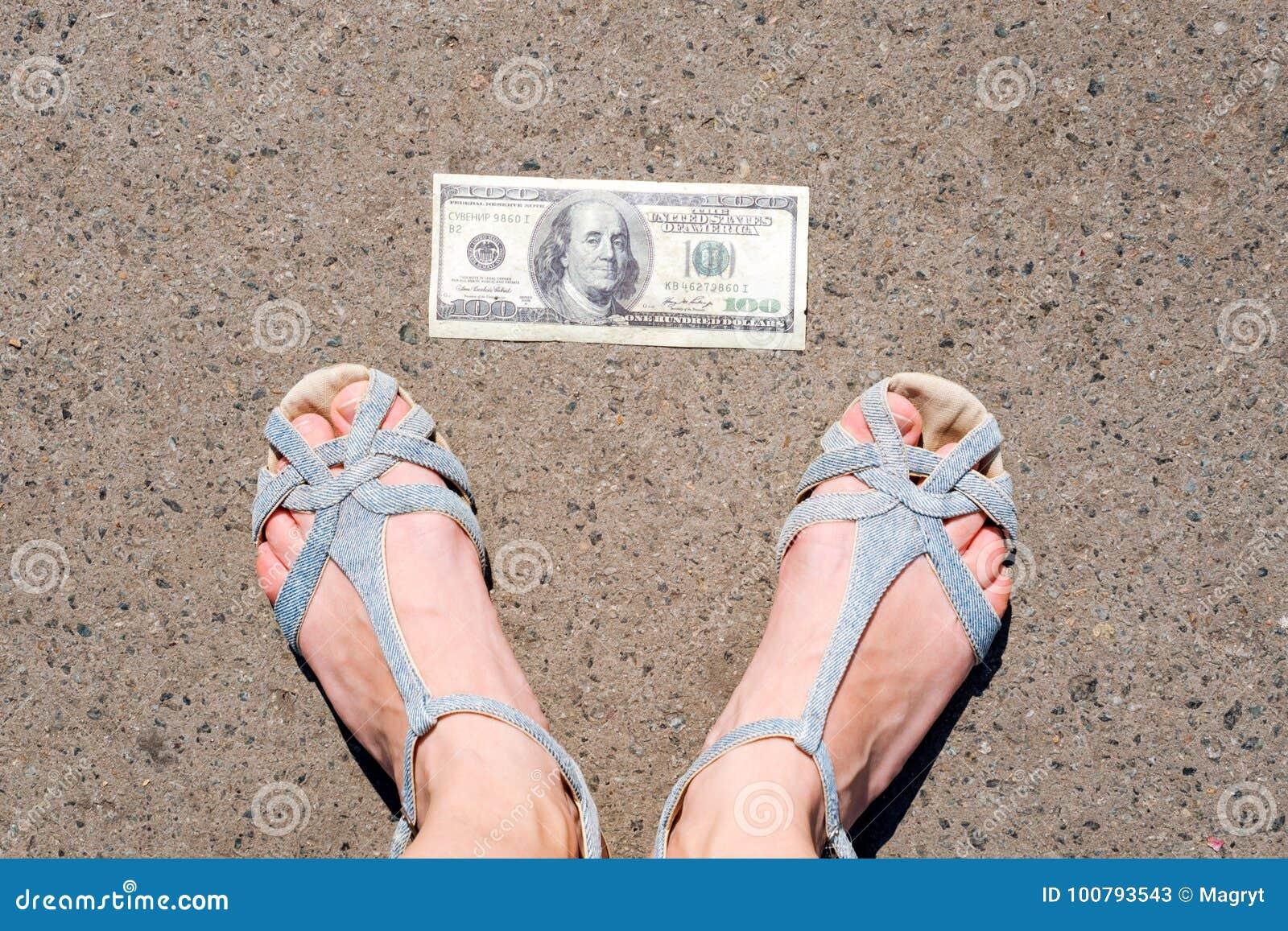 Gelukkige vrouw die geld op de straat vinden Vrouwenvoeten naast honderd dollarsrekening Verloren en gevonden geld die liggen