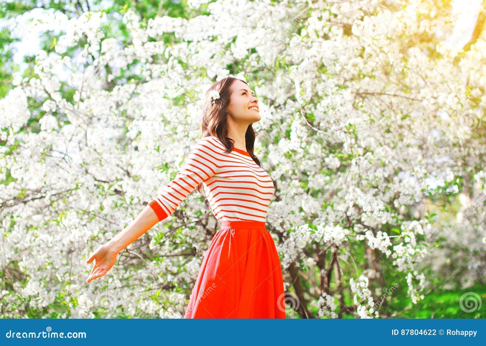 Gelukkige vrouw die geur van bloemen over de lentetuin genieten