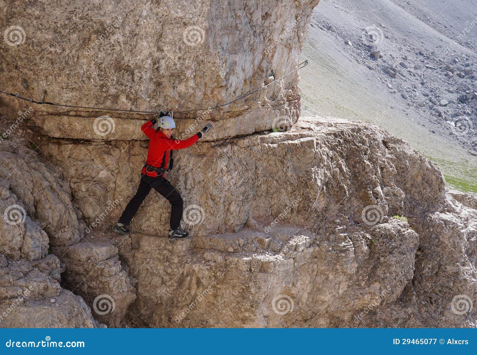 Gelukkige vrouw die op a via ferratasleep beklimmen