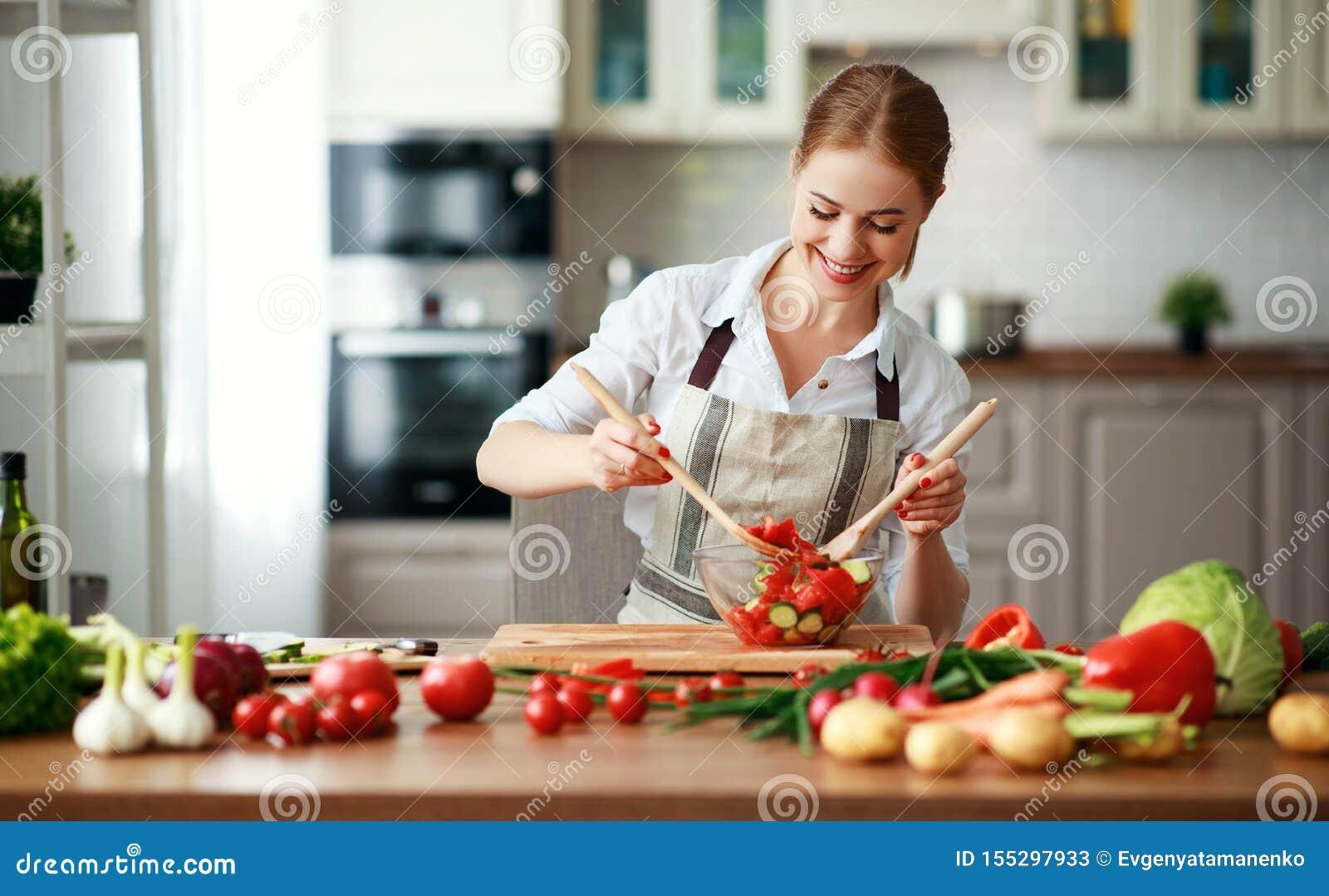 Gelukkige vrouw die plantaardige salade in keuken voorbereiden