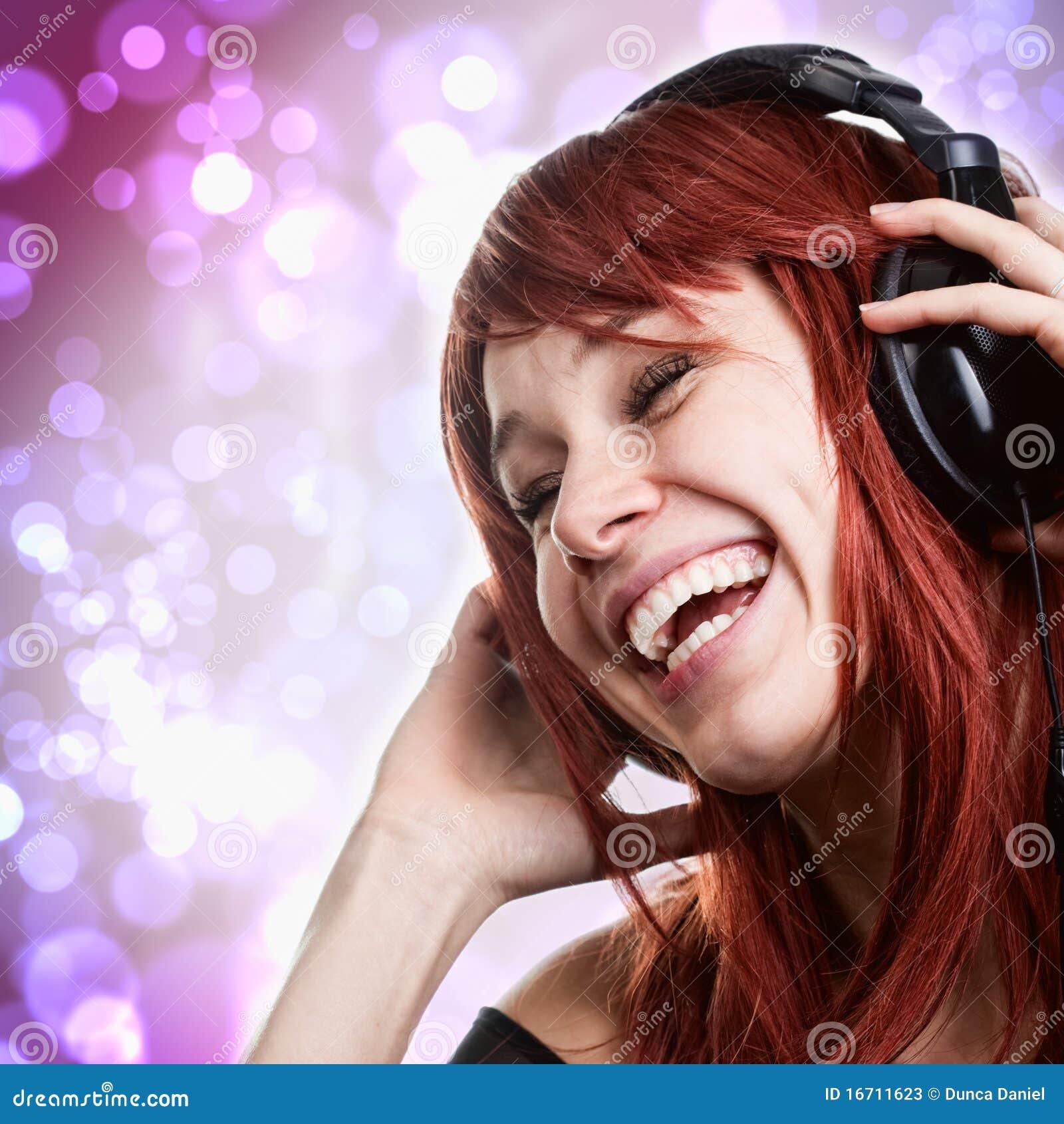 Gelukkige vrouw die pret met muziekhoofdtelefoons heeft