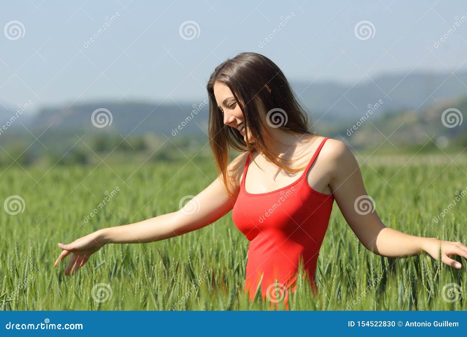 Gelukkige vrouw die tussen tarwe op een gebied lopen