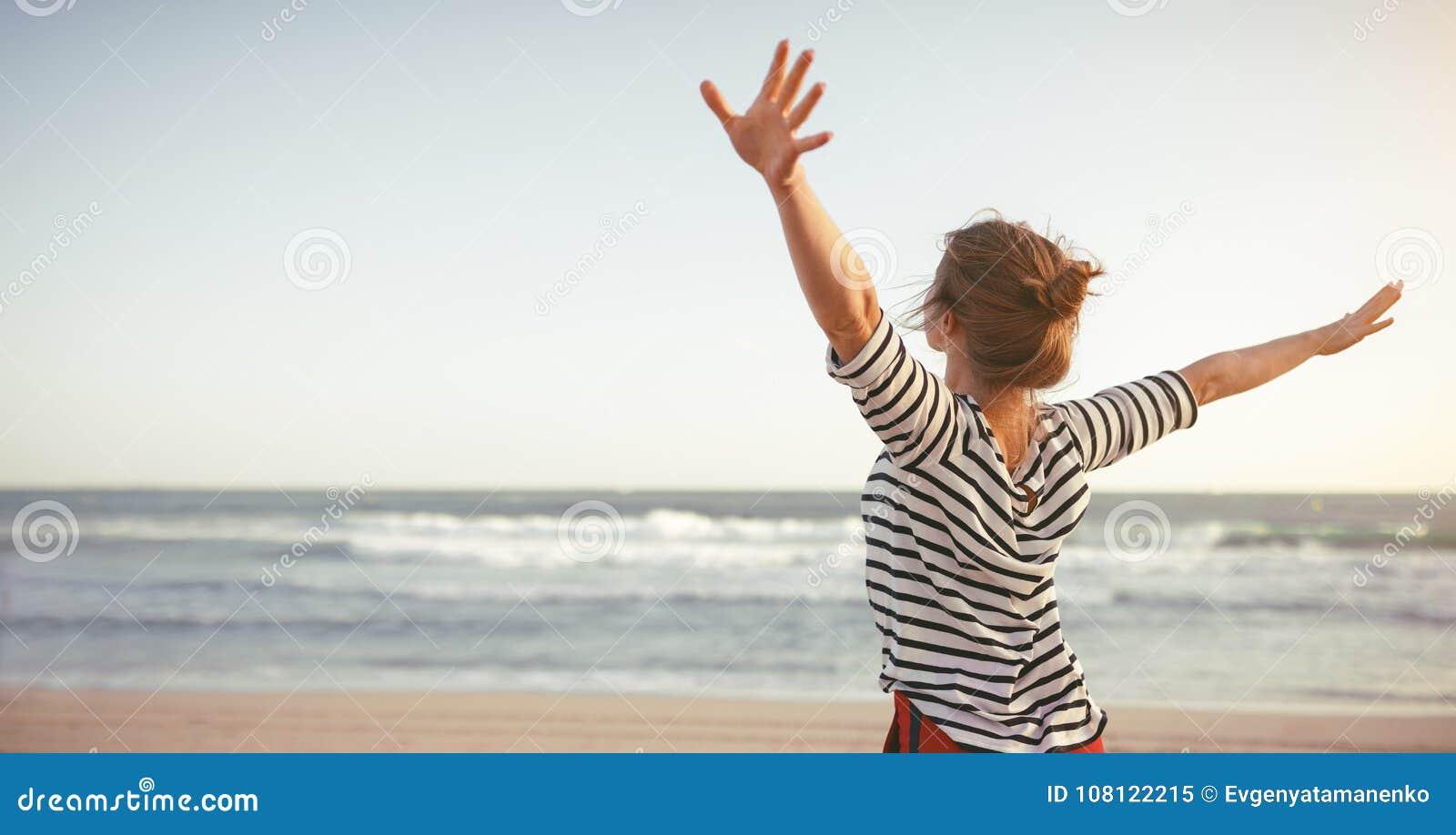 Gelukkige vrouw die van vrijheid met open handen op overzees genieten