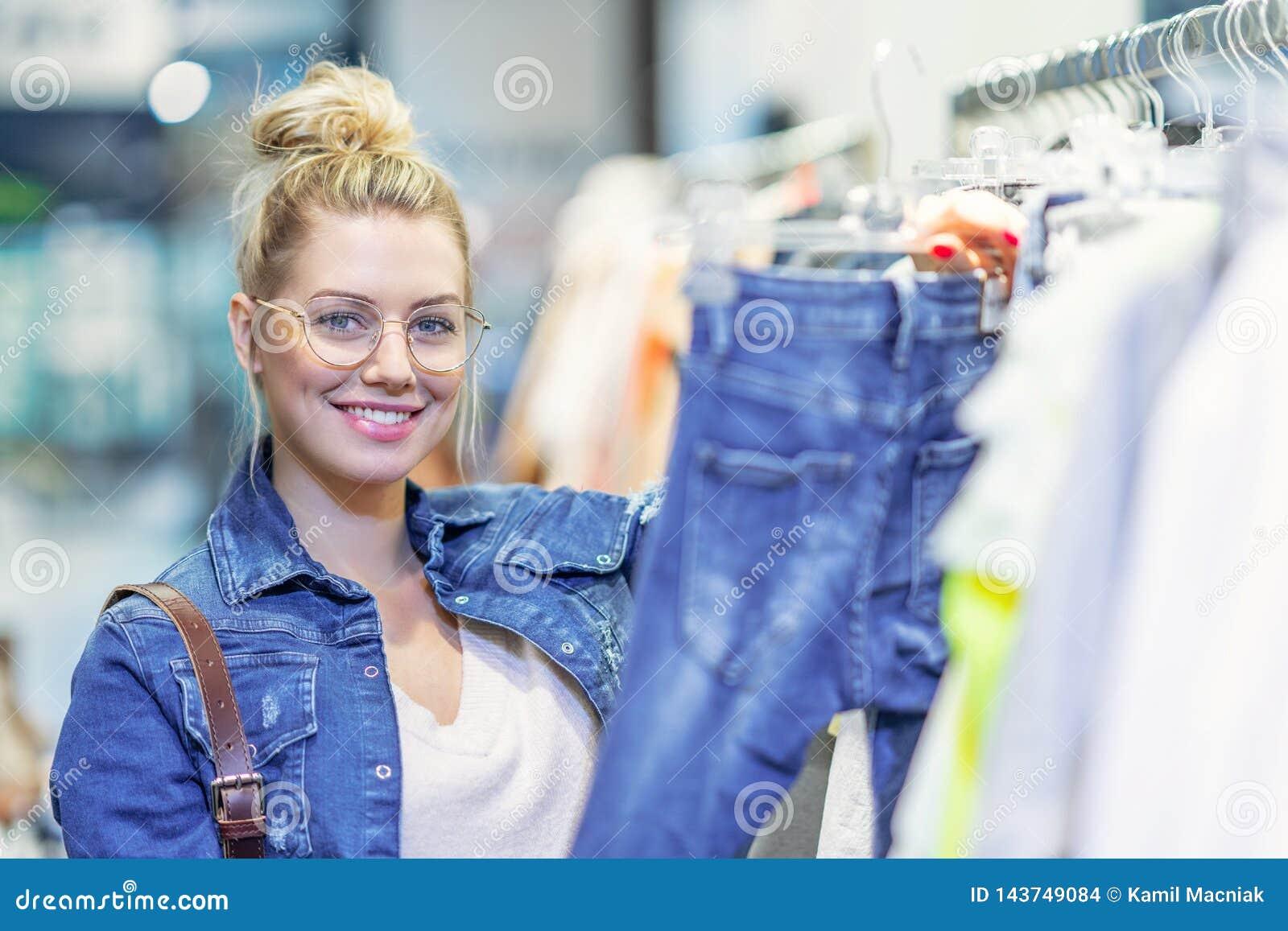 Gelukkige vrouw die voor kleren in opslag winkelen