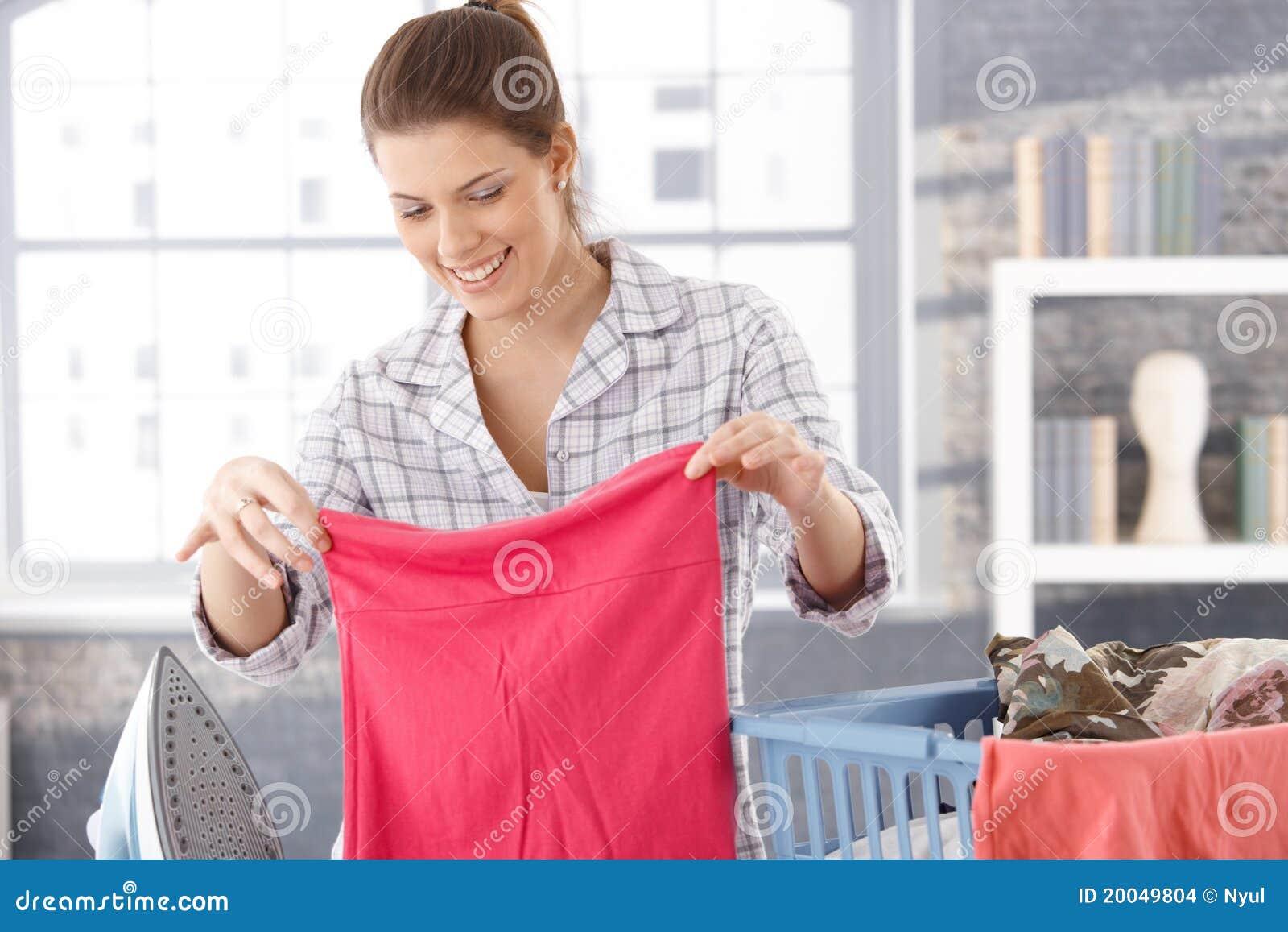 Gelukkige vrouw die wasserij doet