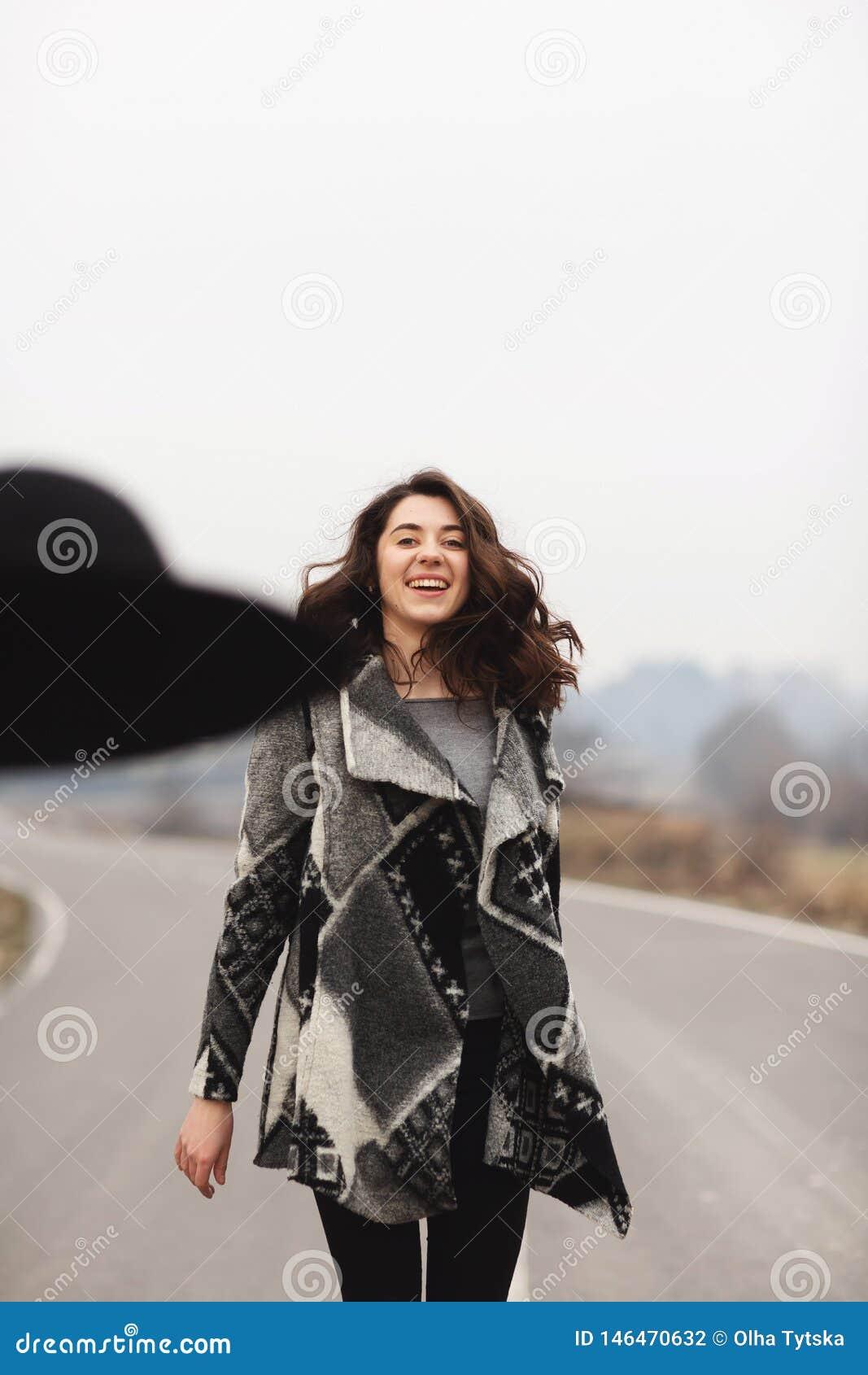 Gelukkige vrouw in een mooie grijze cardigan en zwarte hoedenritten langs de manier