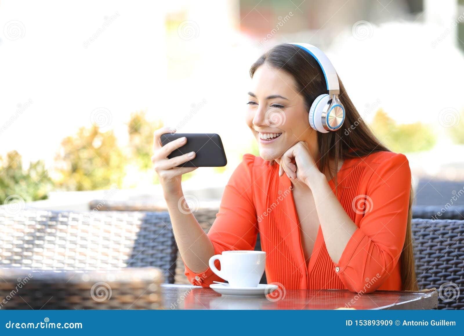 Gelukkige vrouw het letten op media op smartphone in een restaurant