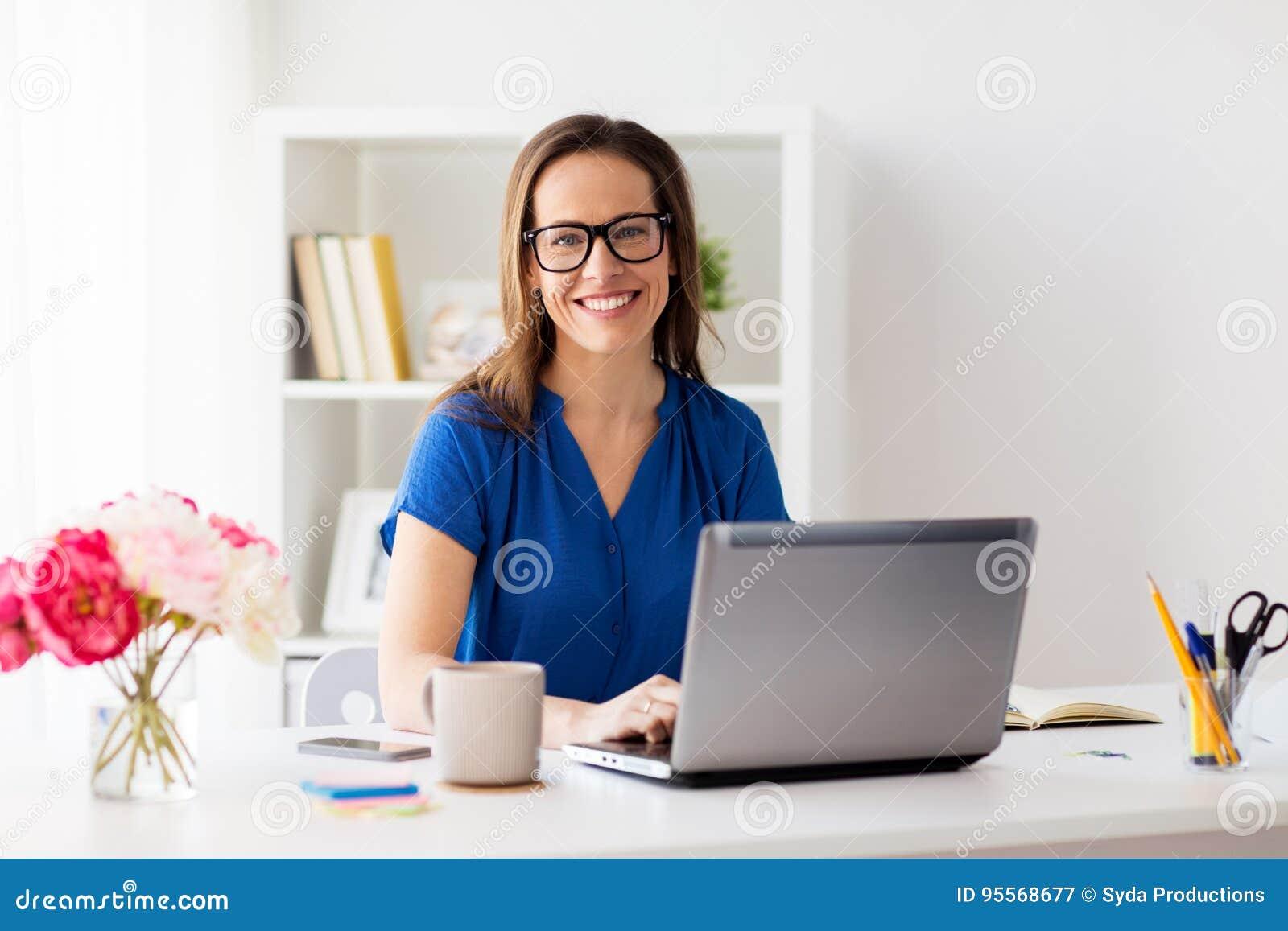 Gelukkige vrouw met laptop thuis of bureau die werken