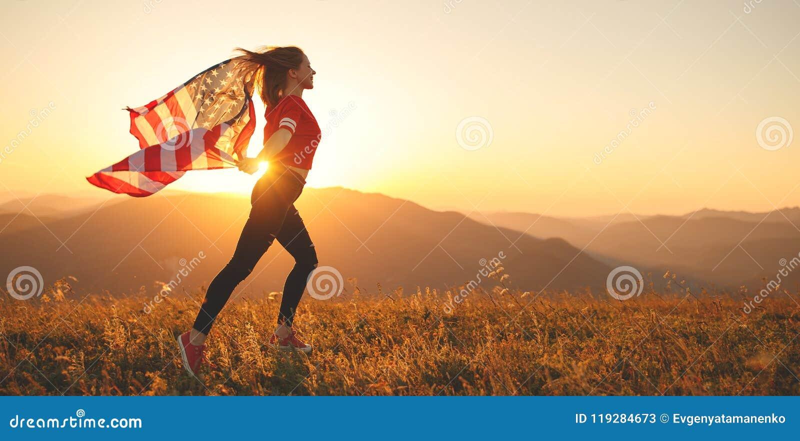 Gelukkige vrouw met vlag van Verenigde Staten die van de zonsondergang op Na genieten
