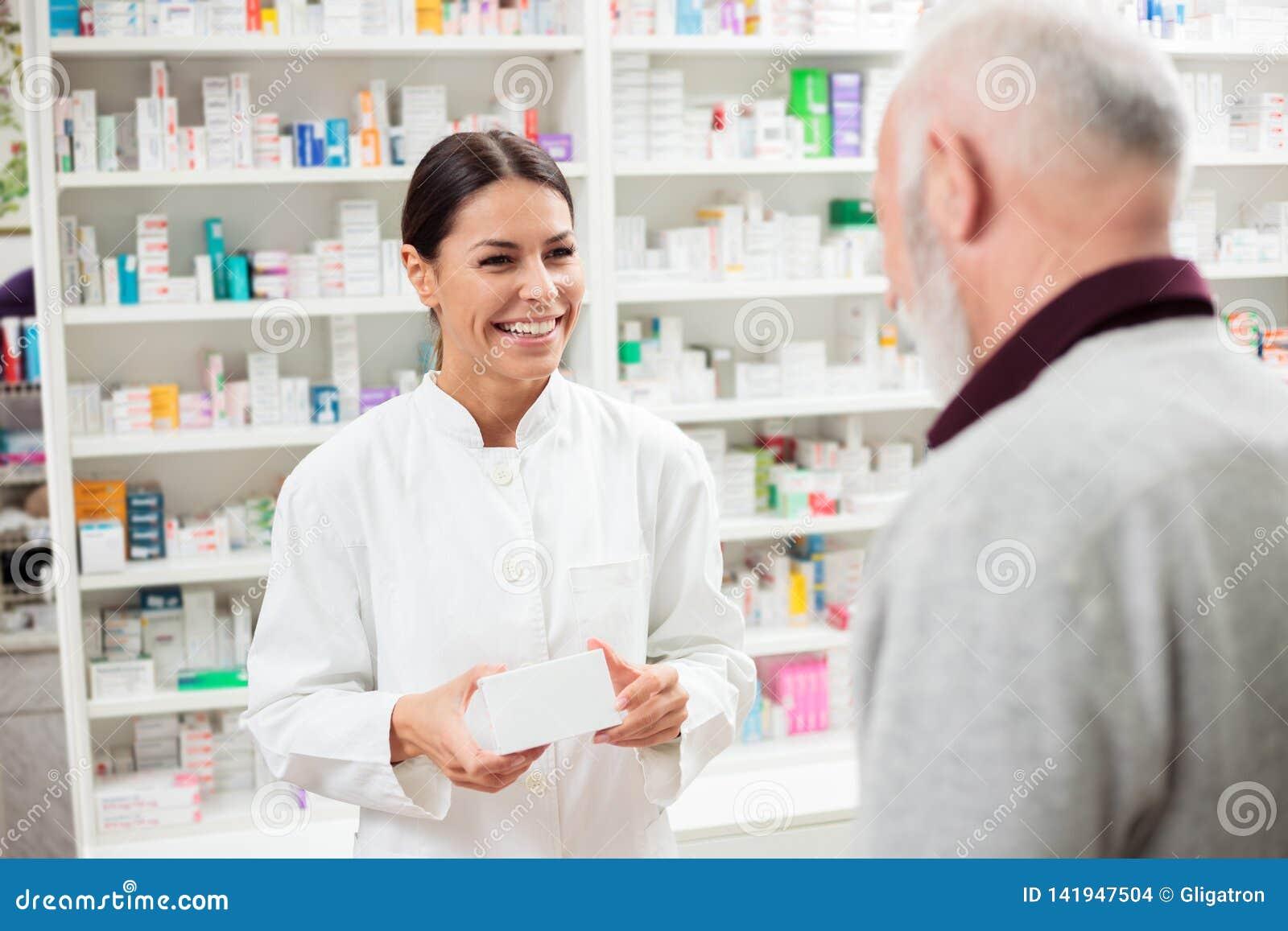 Gelukkige vrouwelijke apotheker die medicijnen geeft aan hogere mannelijke klant